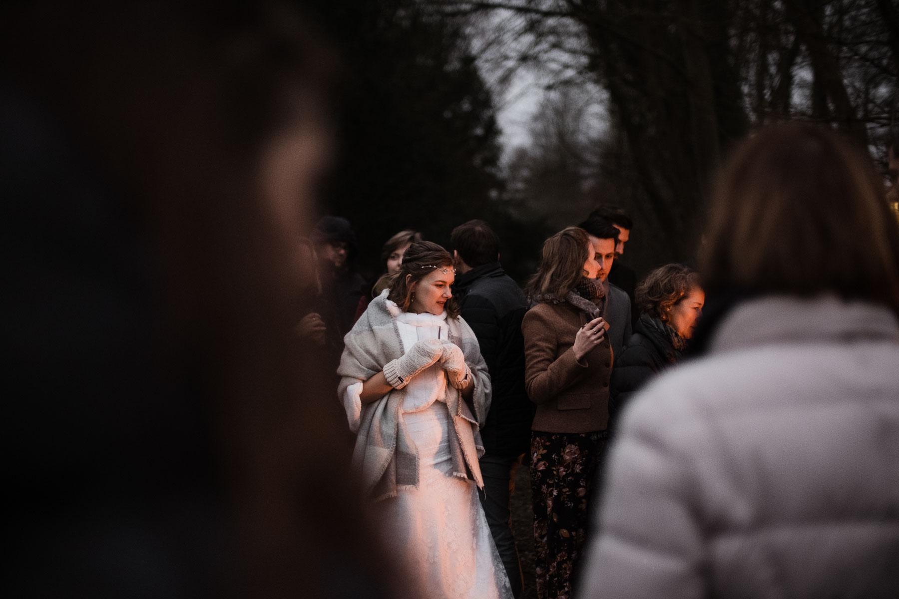 die Braut steht mit ihren Gästn in dem Licht der Feuerschalen, sie hält ein Glas in der Hand, sie trägt über ihren Brautkleid einen Pelzumhang