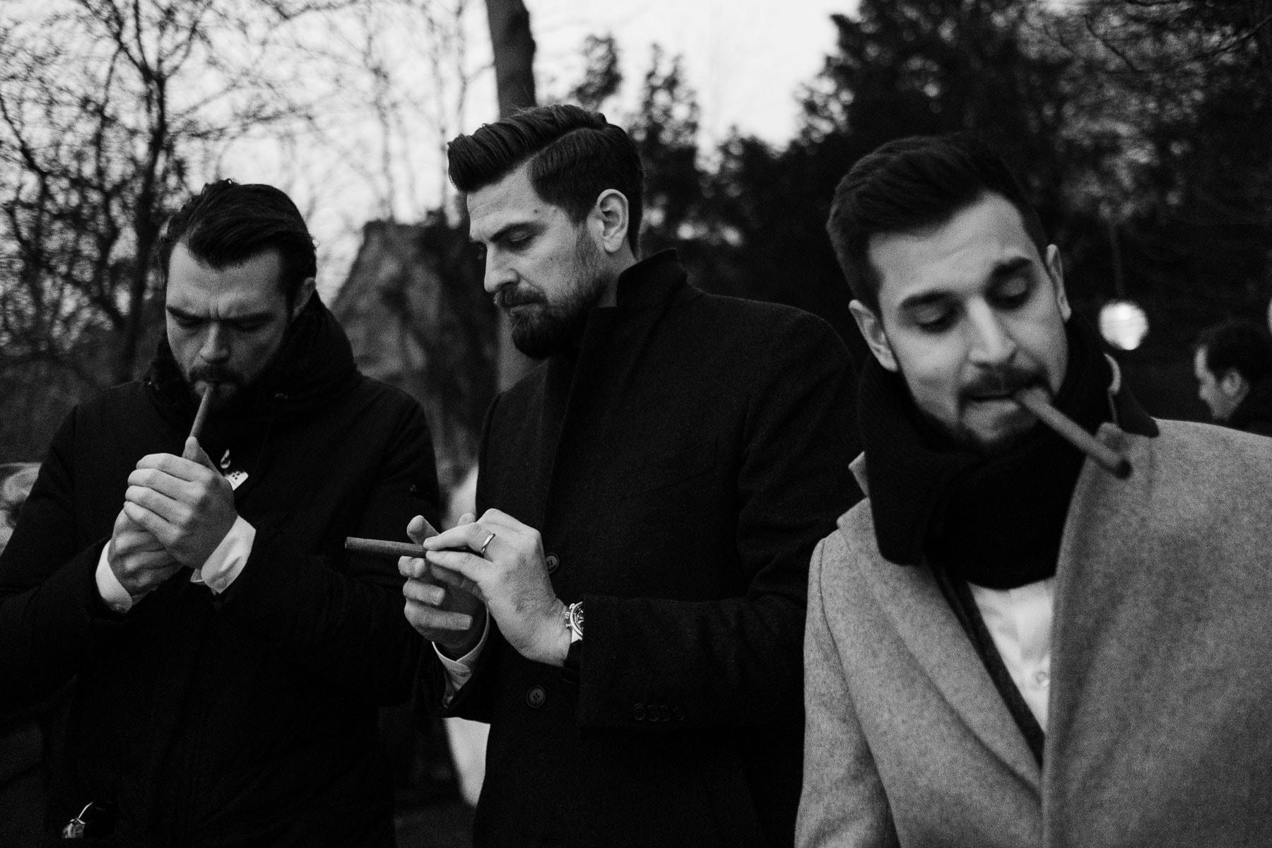 der Bräutigam steht mit 2 Männern draußen, der Bräutigam hat eine Zigarre in dem Mund, ein Mann hat ebenfalls eine Zigarre im Mund und steckt sie gerade an, ein anderer Mann hält seine Zigarre in der Hand