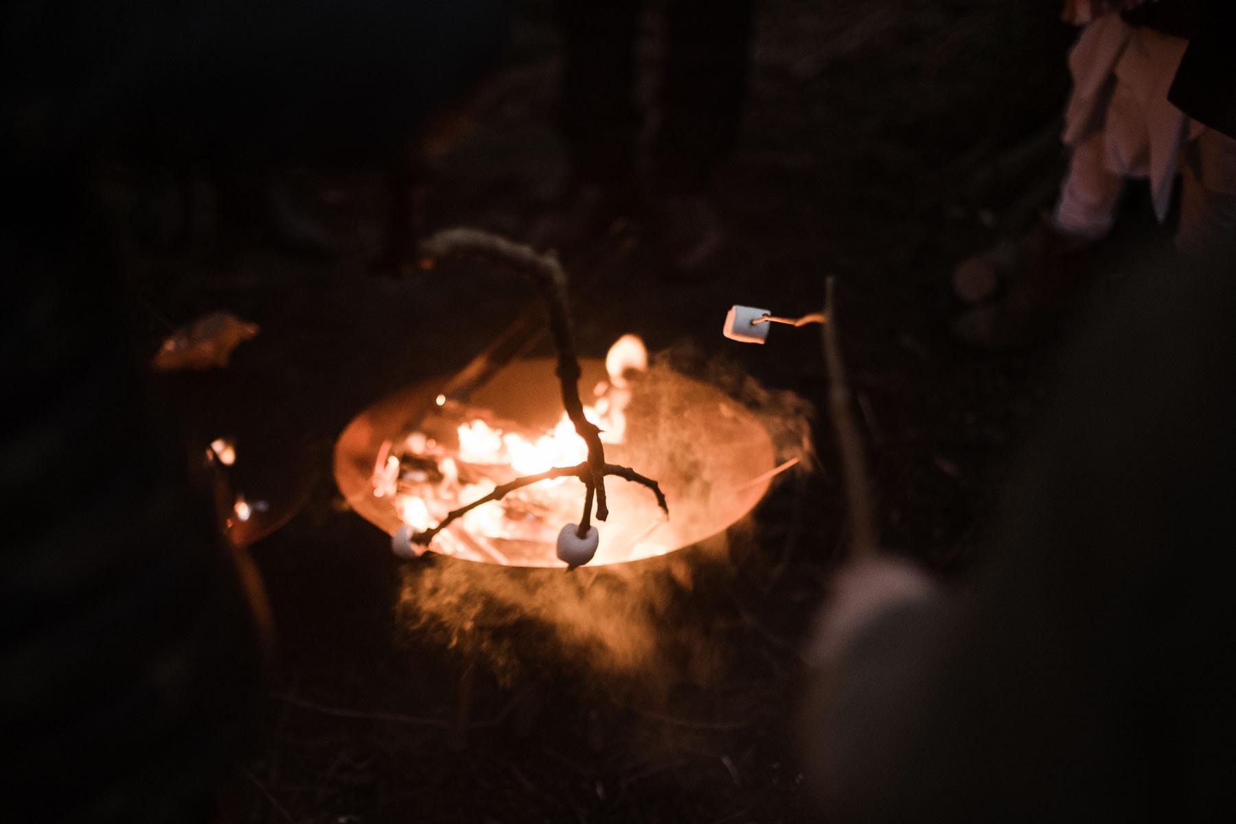 in einer Feuerschale werden Marshmllows auf Stöckern gehalten