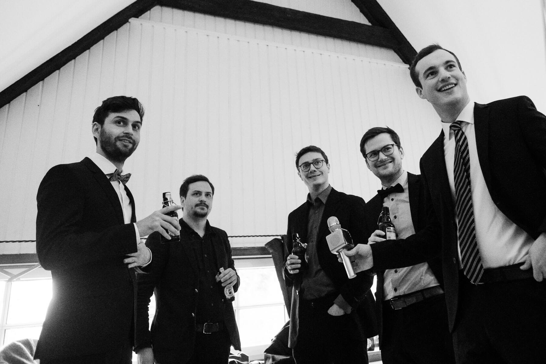 in einem Landhaus stehen 5 Männer zusammen, sie tragen einen Anzug, sie haben eine Flasche in der Hand, ihr Blick ist in die gleiche Richtung gerichtet, hinter ihnen ist ein weißer Holzgiebel zu sehen
