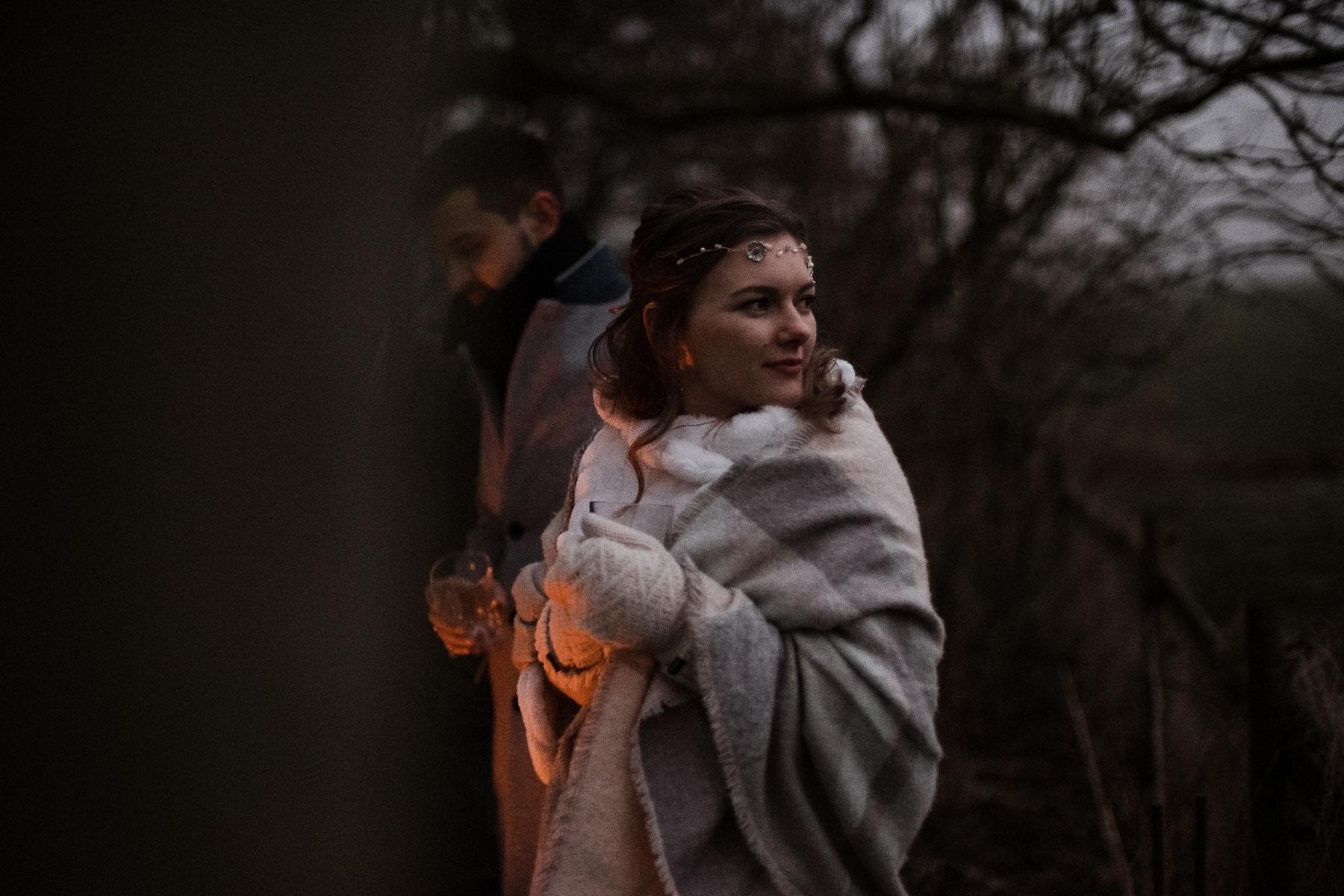 die Braut steht in ihrem Brautkleid in einer Decke gehüllt im Licht der Feuerschale, sie trägt Handschuhe und schaut nach hinten