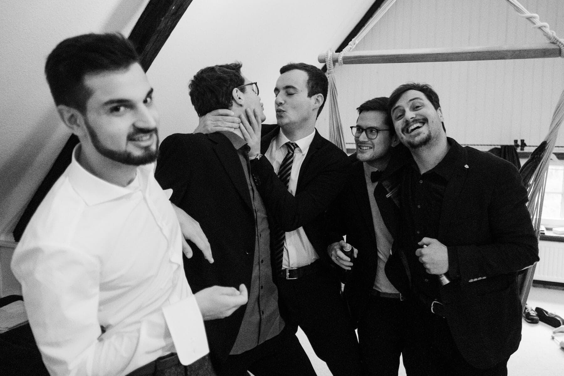 der Bräutigam steht mit 4 weiteren Männern in einem alten Landhaus, der Bräutigam trägt ein weißes Hemd, er schaut direkt in die Kamera, die 4 Männer tragen einen Anzug, sie verziehen alle das Gesicht und lachen dabei