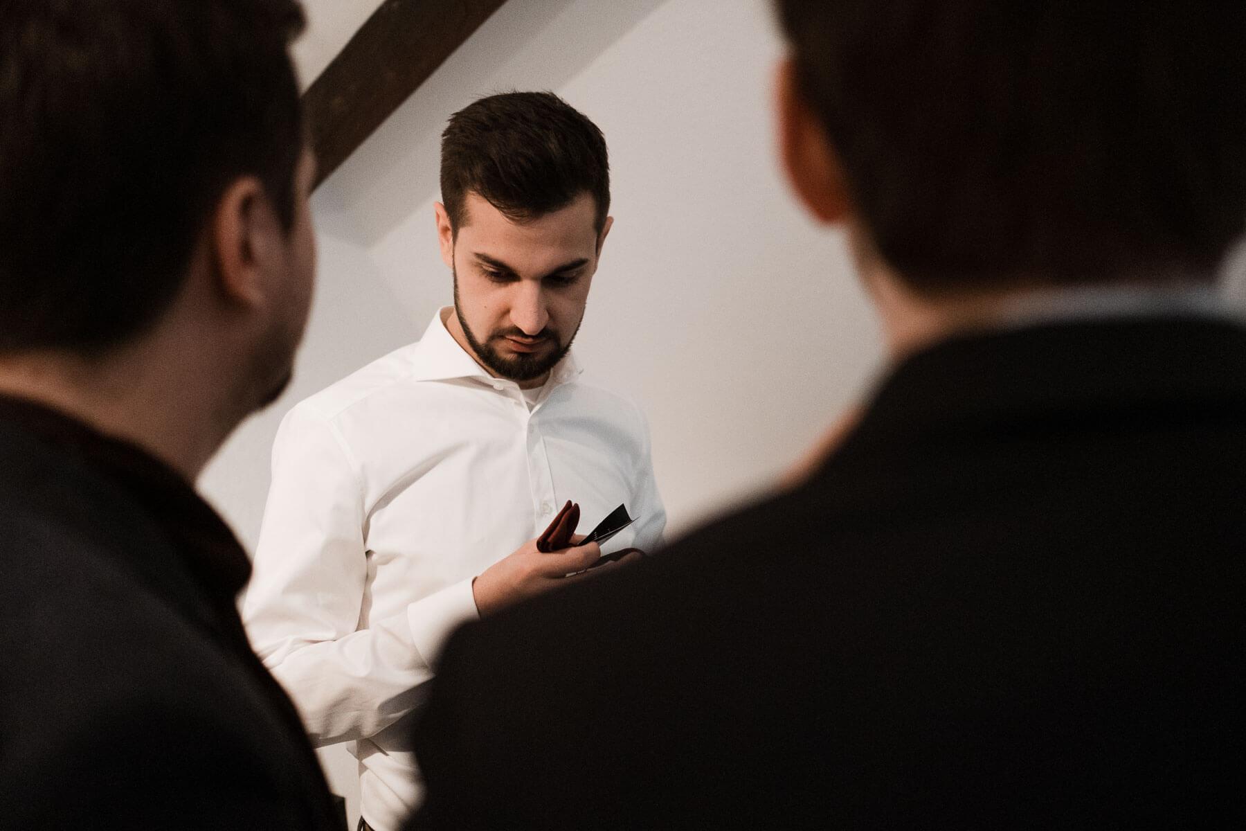 der Bräutigam steht in einem Raum, er trägt ein weißes Hemd und schaut auf sein Smartphone, vor ihm stehen 2 weitere Männer