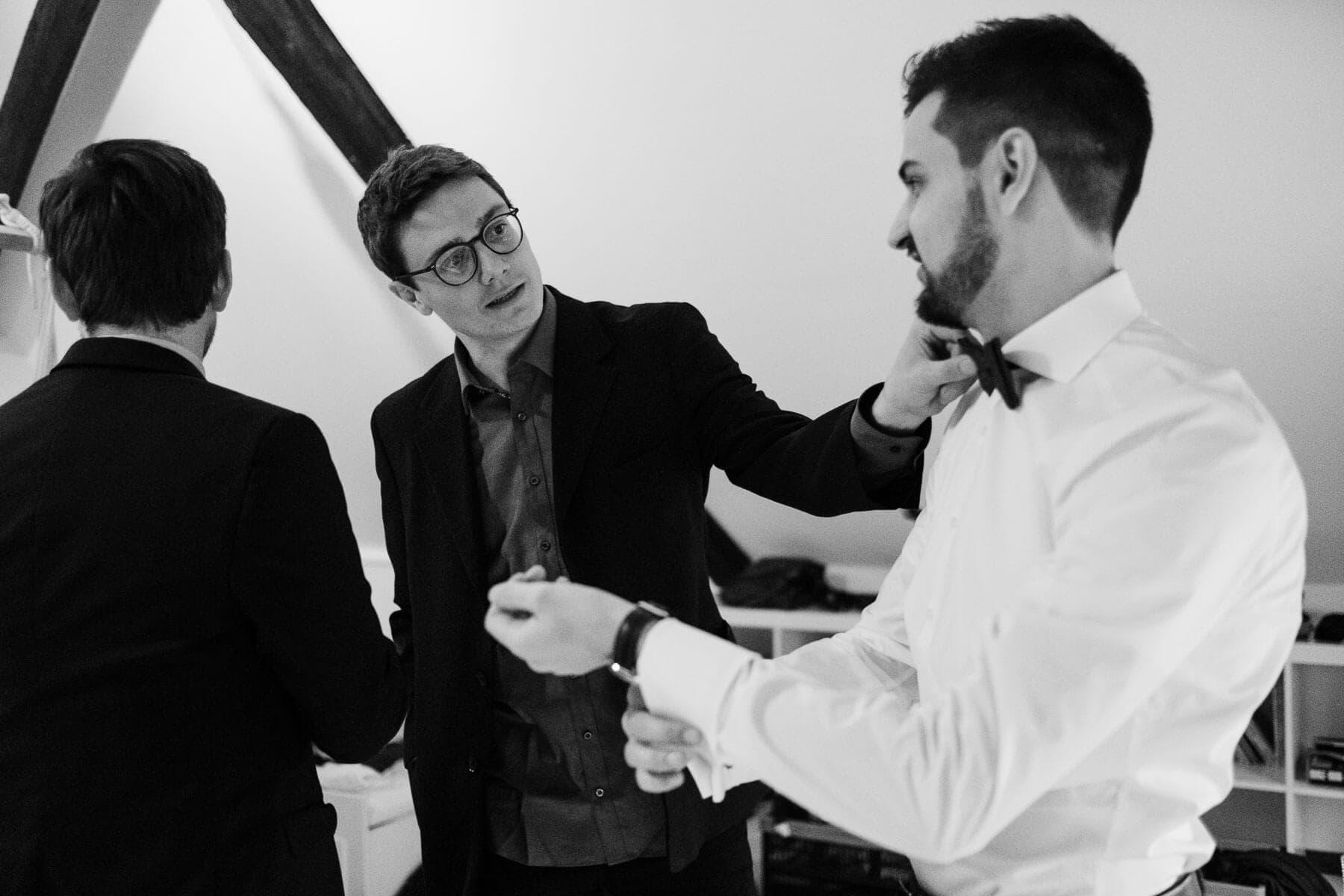 der Bräutigam steht mit 2 Männern in einem Landhaus, er trägt ein weißes Hemd, er richtet sich die Manschette, ein Mann steht neben ihm und legt seine Hand auf seine Schulter, sie schauen sich an, der andere Mann steht mit dem Rücken zum Bräutigam