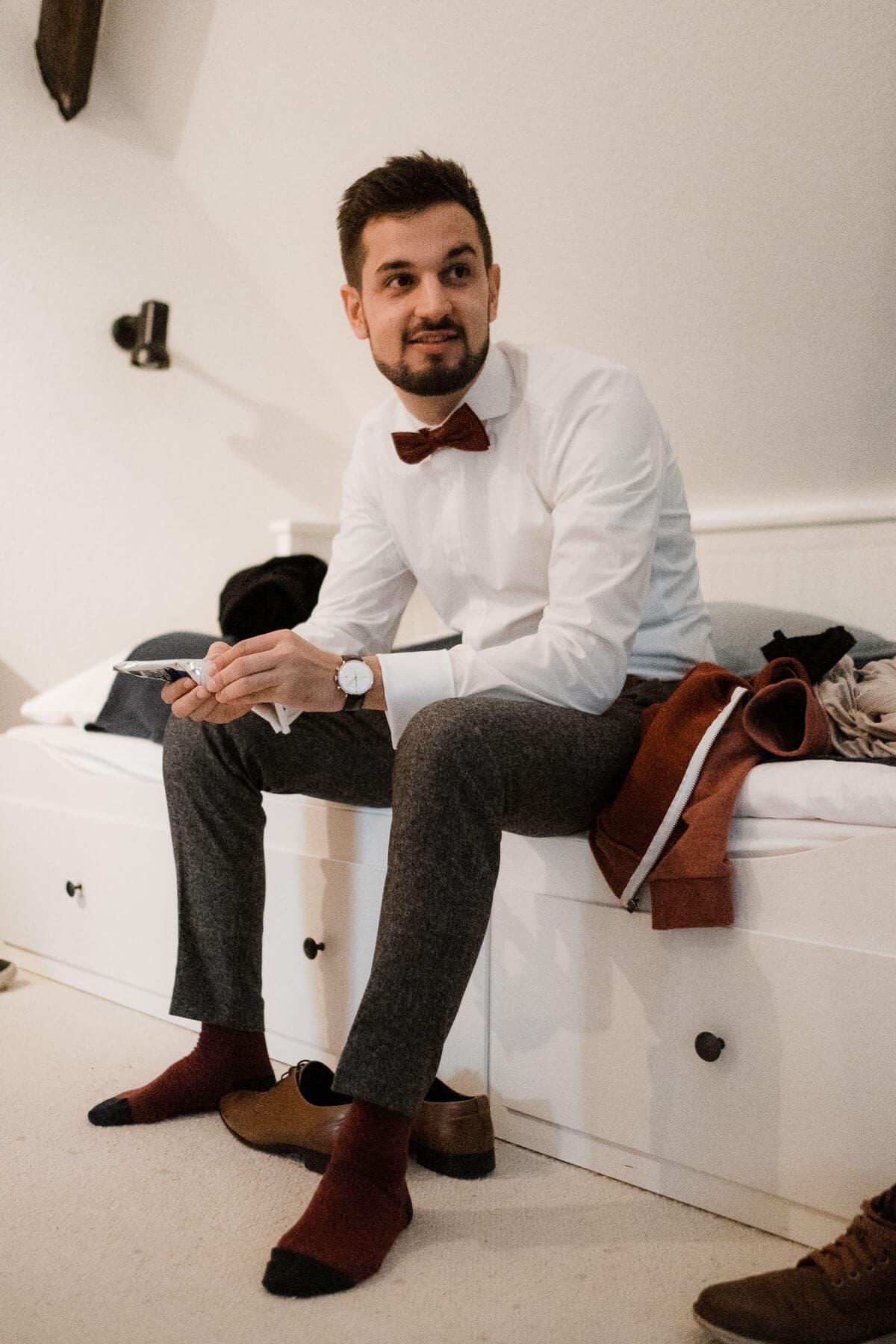 der Bräutigam sitzt in einem Dachzimmer auf einem Bett, er trägt ein weißes Hemd und eine Fliege, er trägt rote Socken, sein Blick ist zur Seite gerichtet