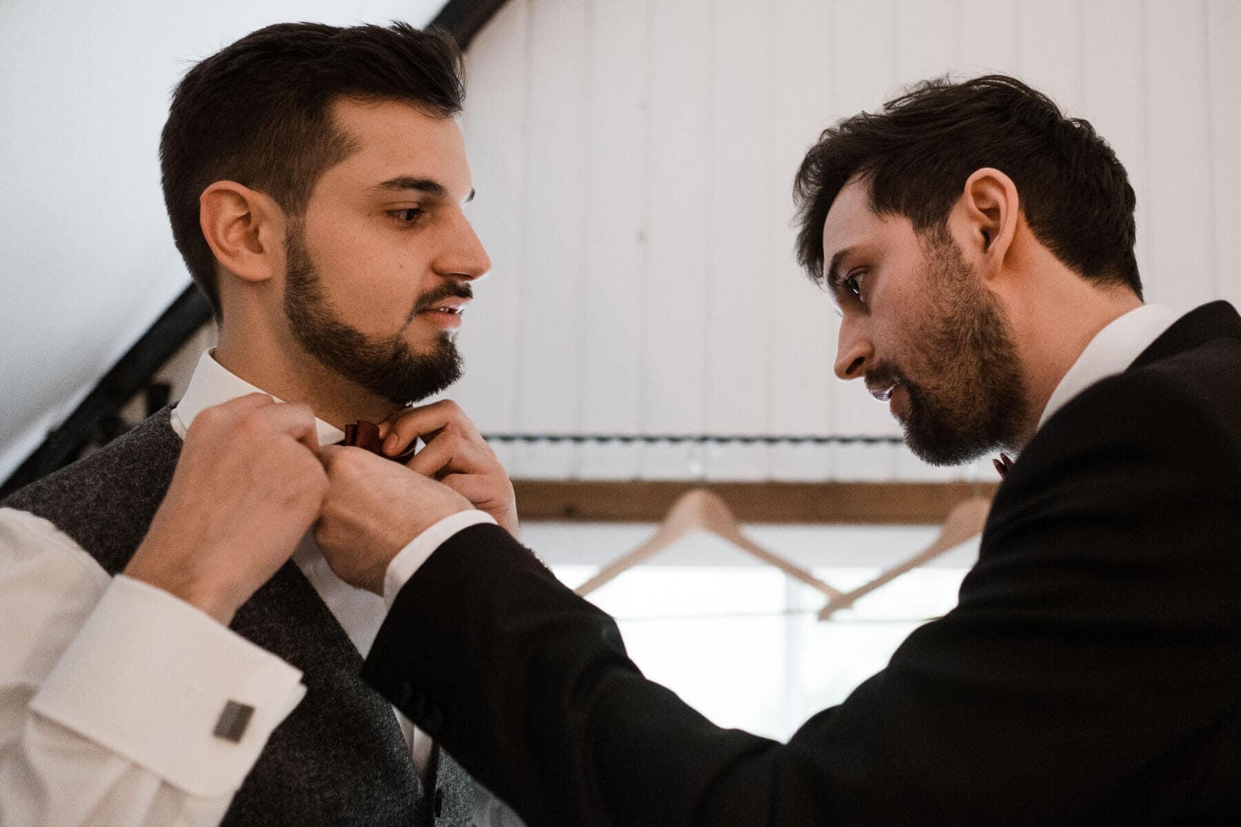 der Bräutigam steht mit einem weiteren Mann in einem Zimmer in einem Landhaus, der Bräutigam trägt ein weißes Hemd und eine Weste, sowie eine Fliege, der andere Mann trägt einen schwarzen Anzug, er richtet dem Bräutigam die Fliege