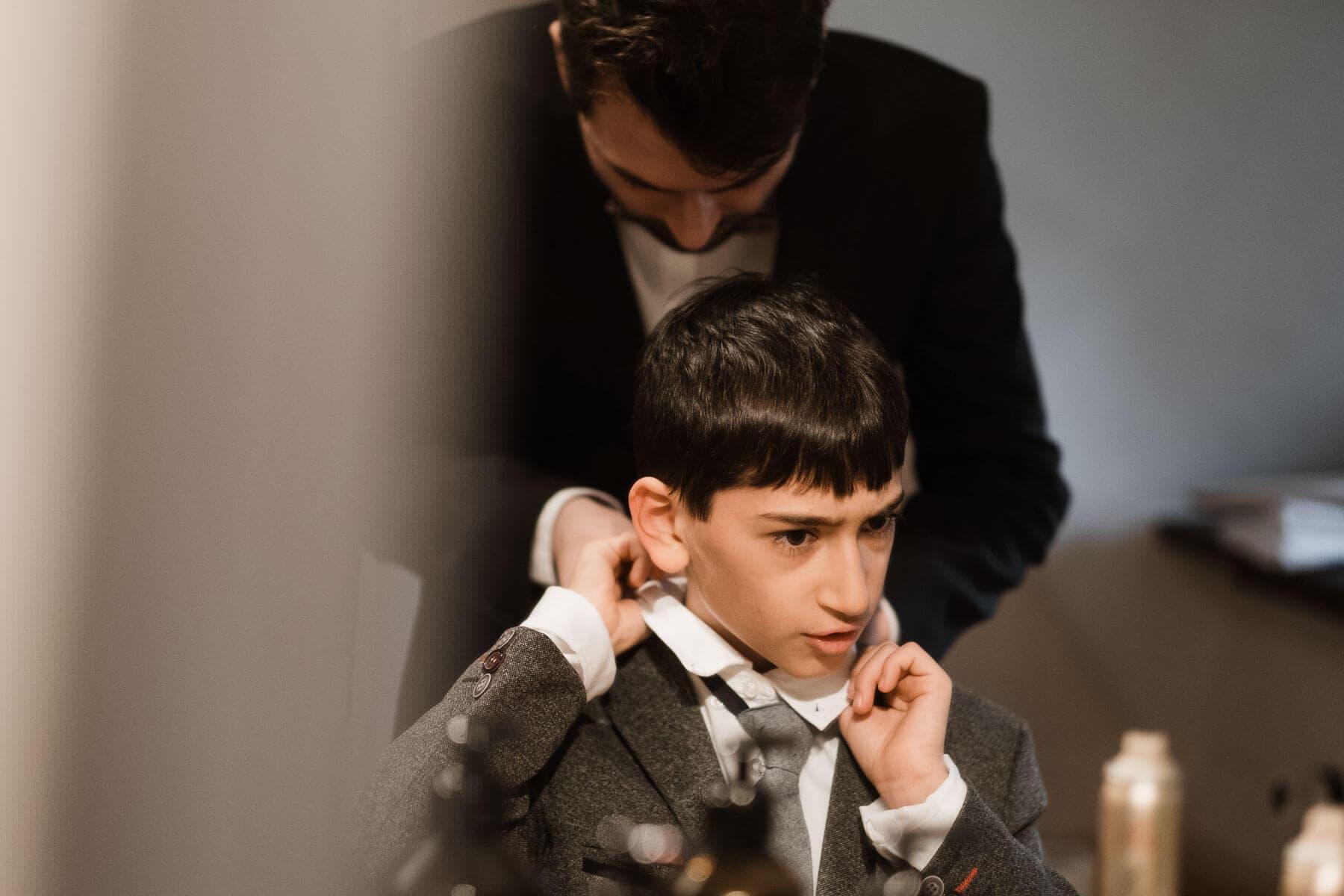 ein kleiner Junge sitzt vor einem Spiegel in einem Landhaus, er schaut mit einem kritischen Blick in den Spiegel, hinter ihm steht ein Mann, der dem Jungen die Krawatte richtet