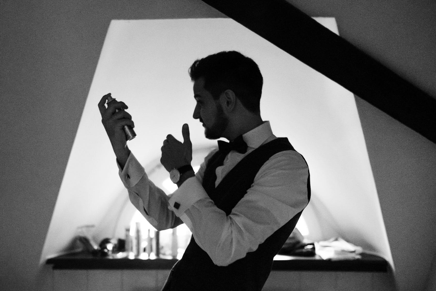 der Bräutigam steht in einem Dachzimmer in einem Landhaus, er trägt ein weißes Hemd, eine Weste und eine Fliege, er hält Haarspray in der Hand und richtet sich seine Haare