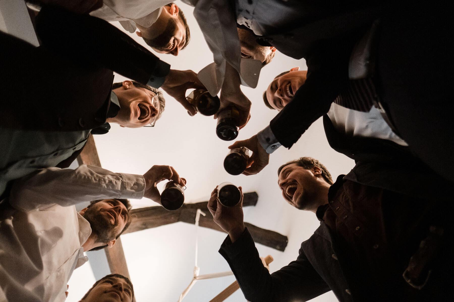 der Bräutigam steht mit 5 weiteren Männern in einem Kreis, sie alle halten eine Flasche in der Hand und stoßen an, zu sehen ist es aus der Froschperspektive