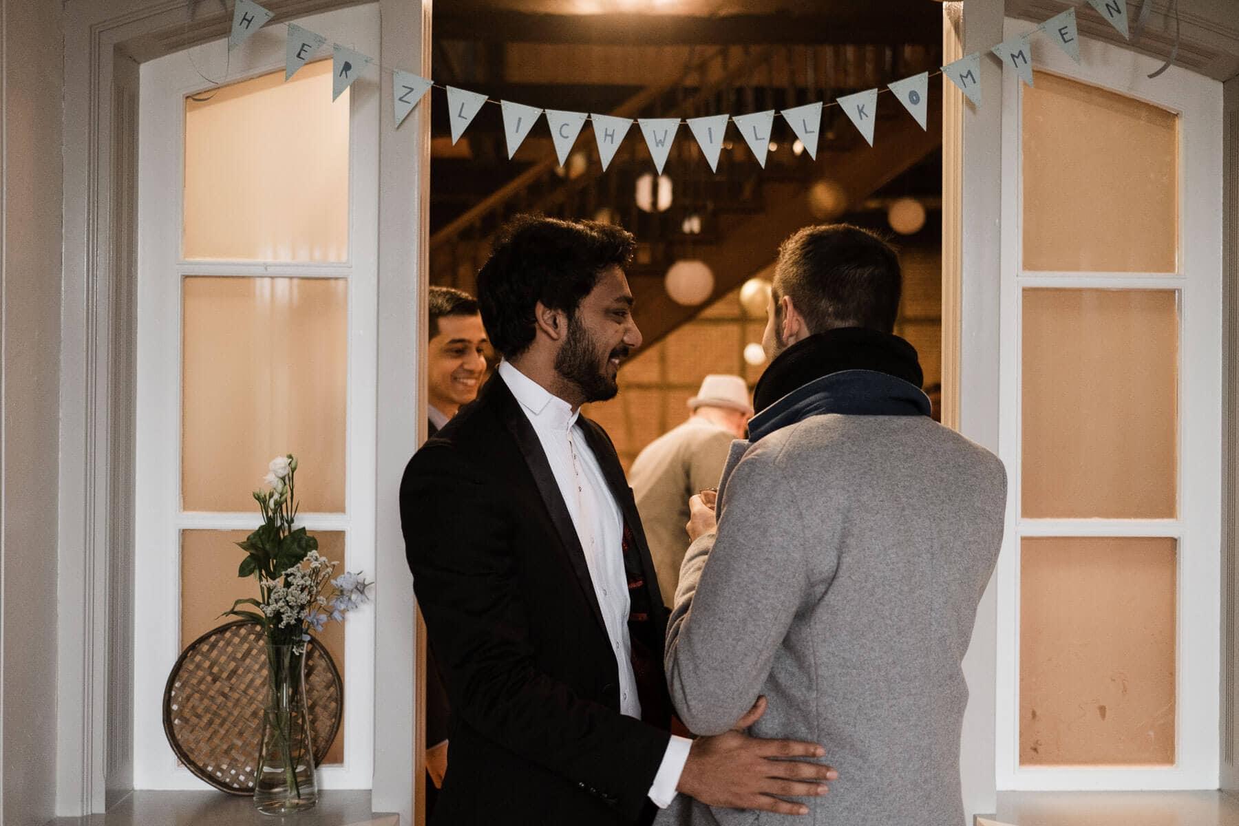 der Bräutigam stheht an einer großen Flügeltür in einem Landhaus, über der Tür hängt eine Wimpelkette, der Bräutigam trägt einen grauen Anzug, der Mann neben ihm trägt einen schwarzen Anzug, er hält seine Hand an den Rücken des Bräutigam