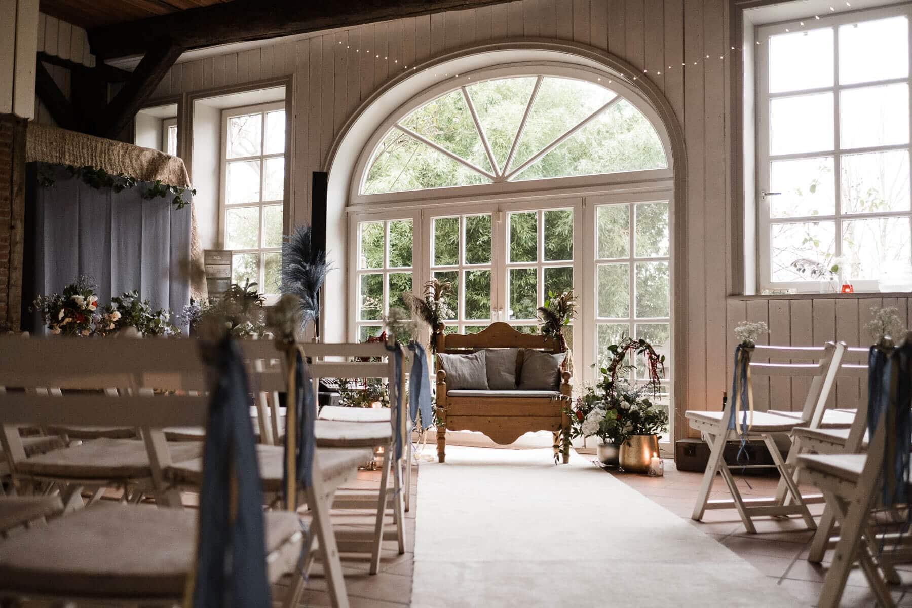 die Trauungslocation in einem Landhaus hat große, helle Sprossenfenster und eine große, runde Tür, vor dieser Tür steht eine gepolsterte Holzbank, sie ist geschmückt mit Blumen, vor der Bank stehen in Reihen gestellte, weiße Klappstühle, welche auch mit Blumen geschmückt sind