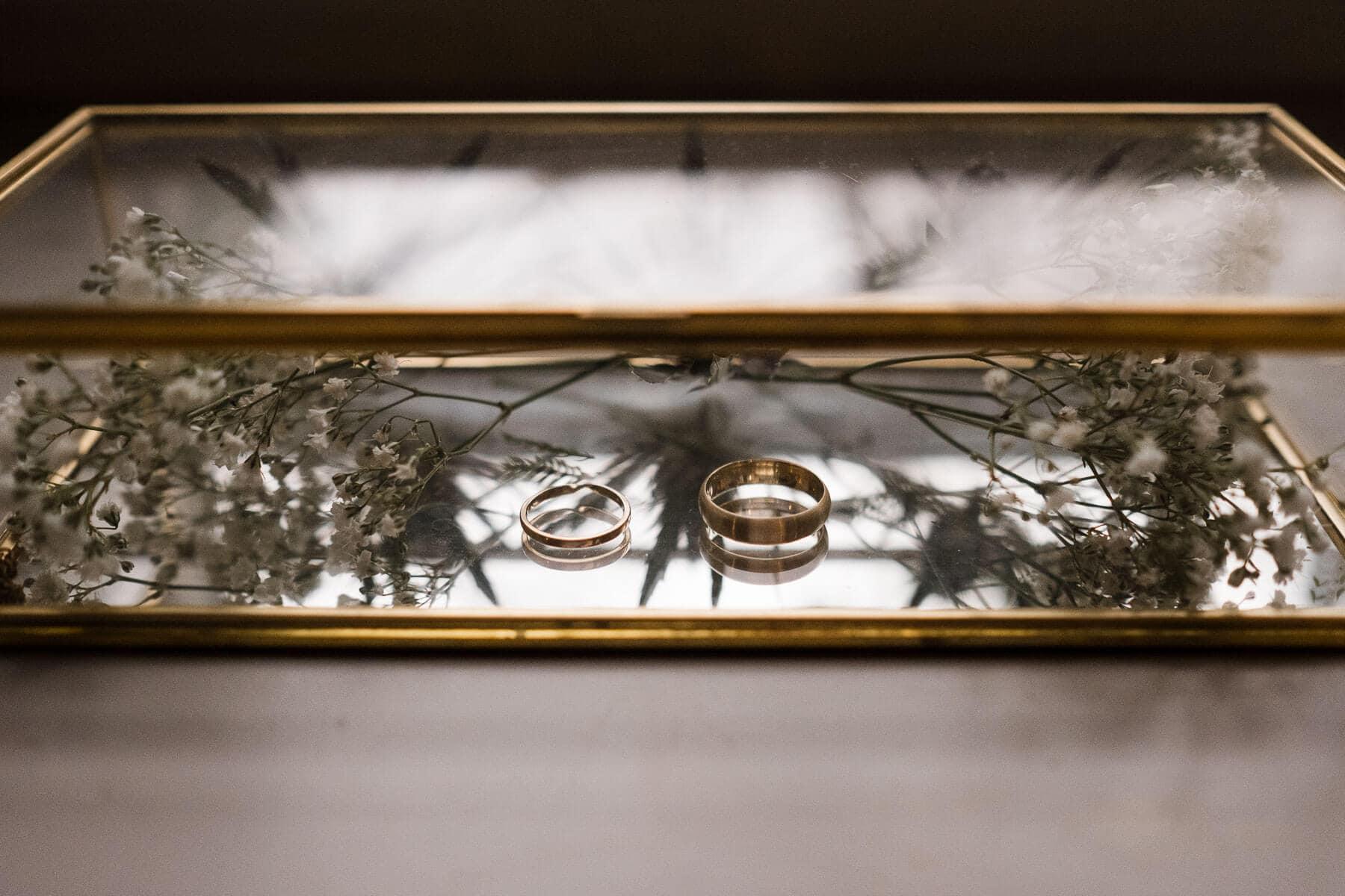 in einem Glaskasten, welcher einen goldenen Rand hat, liegen die goldenen Eheringe, ebenfalls in dem Glaskasten liegt Schleierkraut