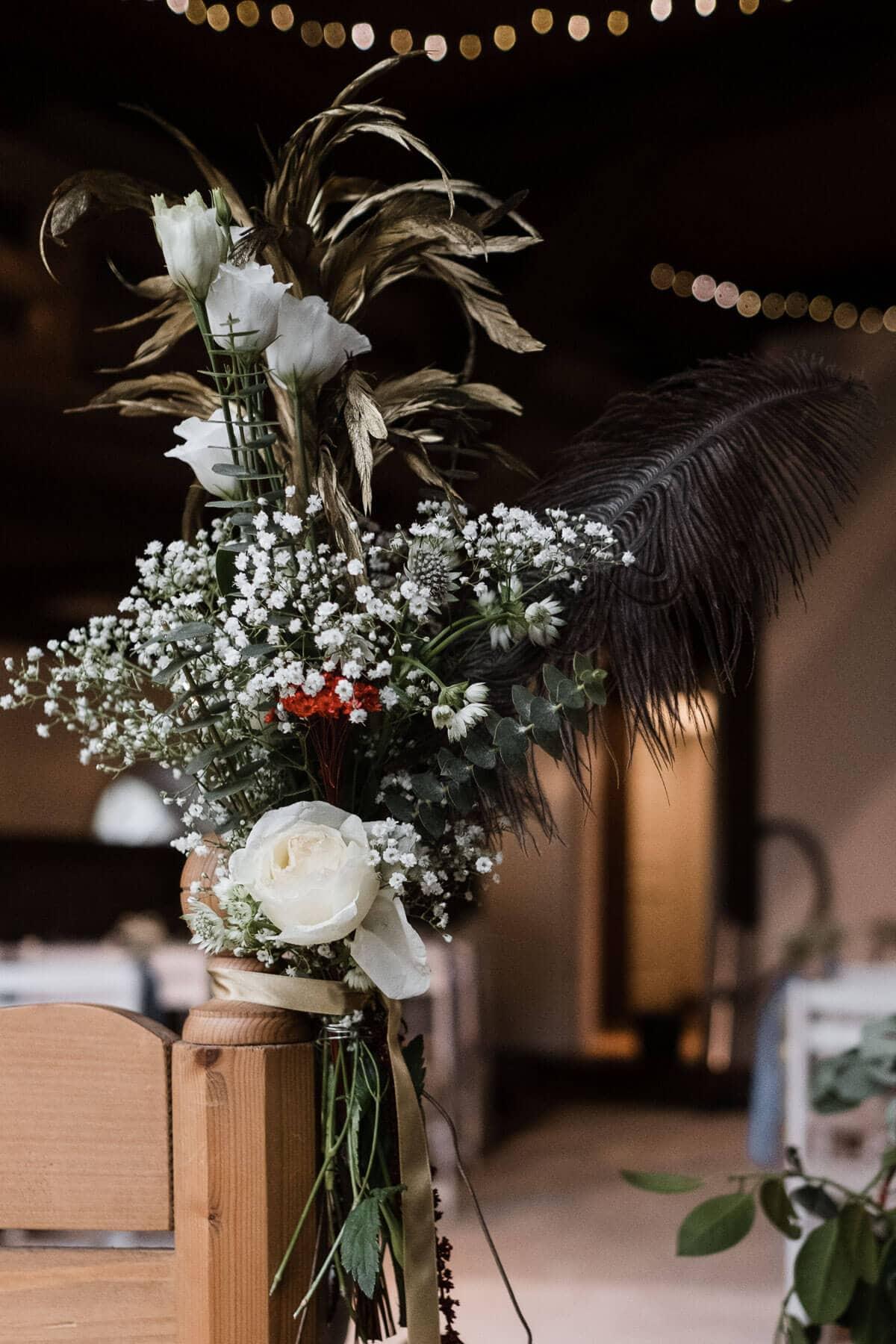 an einer Holzbank in einem Landhaus ist ein großer Blumenstrauß befestigt, in dem Blumenstrauß sind u.a. Blumen, Schleierkraut und eine große Feder