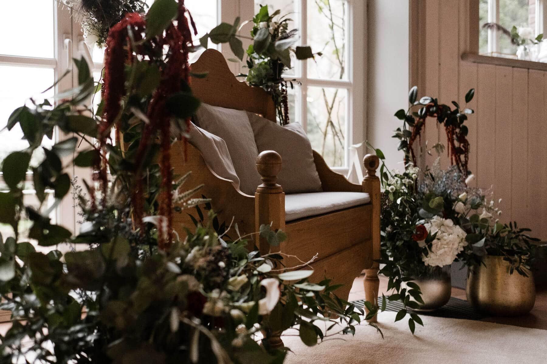 vor einer großen, hellen Holzbogentür in einem Landhaus steht eine gepolsterte Holzbank, sie ist mit Blumen und Grünschnitt geschmückt