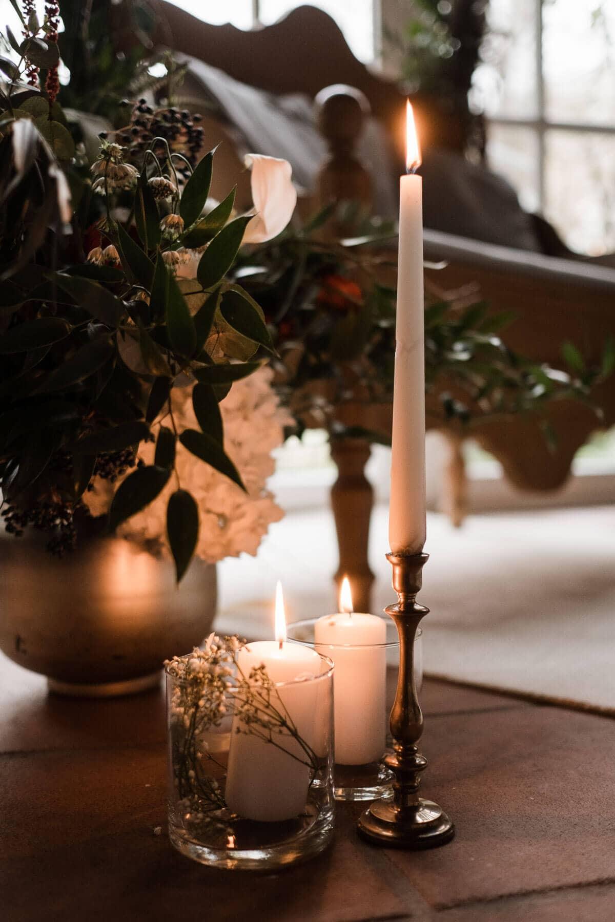auf einem kleinen Holztisch stehen 2 Gläser mit Kerzen, eine große Vase mit Blumen, sowie ein Kerzenständer mit einer Kerze, im Hintergrund ist eine geschmückte Holzbank zu sehen