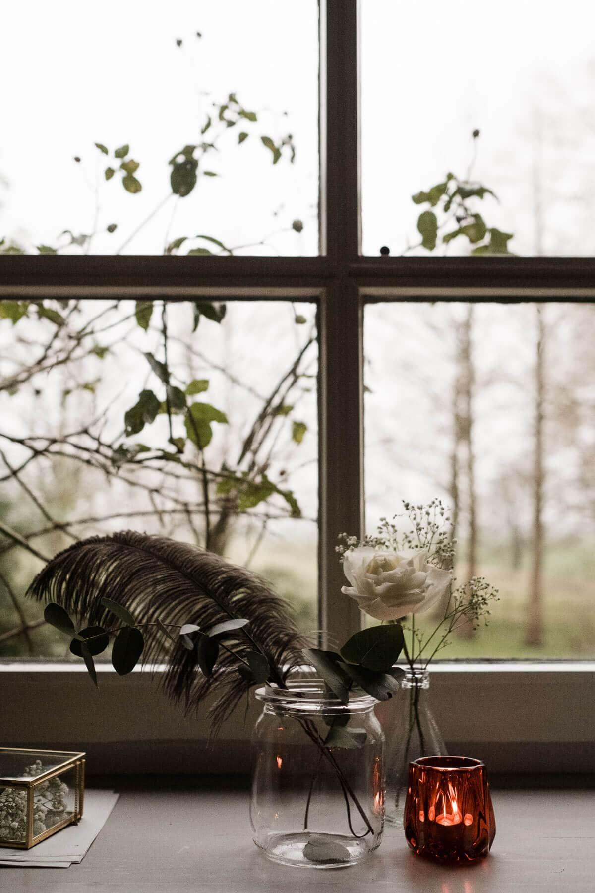 vor einem Sprossenfenster in einem Landhaus steth eine Glasvase mit einer Feder, sowie eine Vase mit einer Blume, draußen vor dem Fenster steht ein grüner Strauch