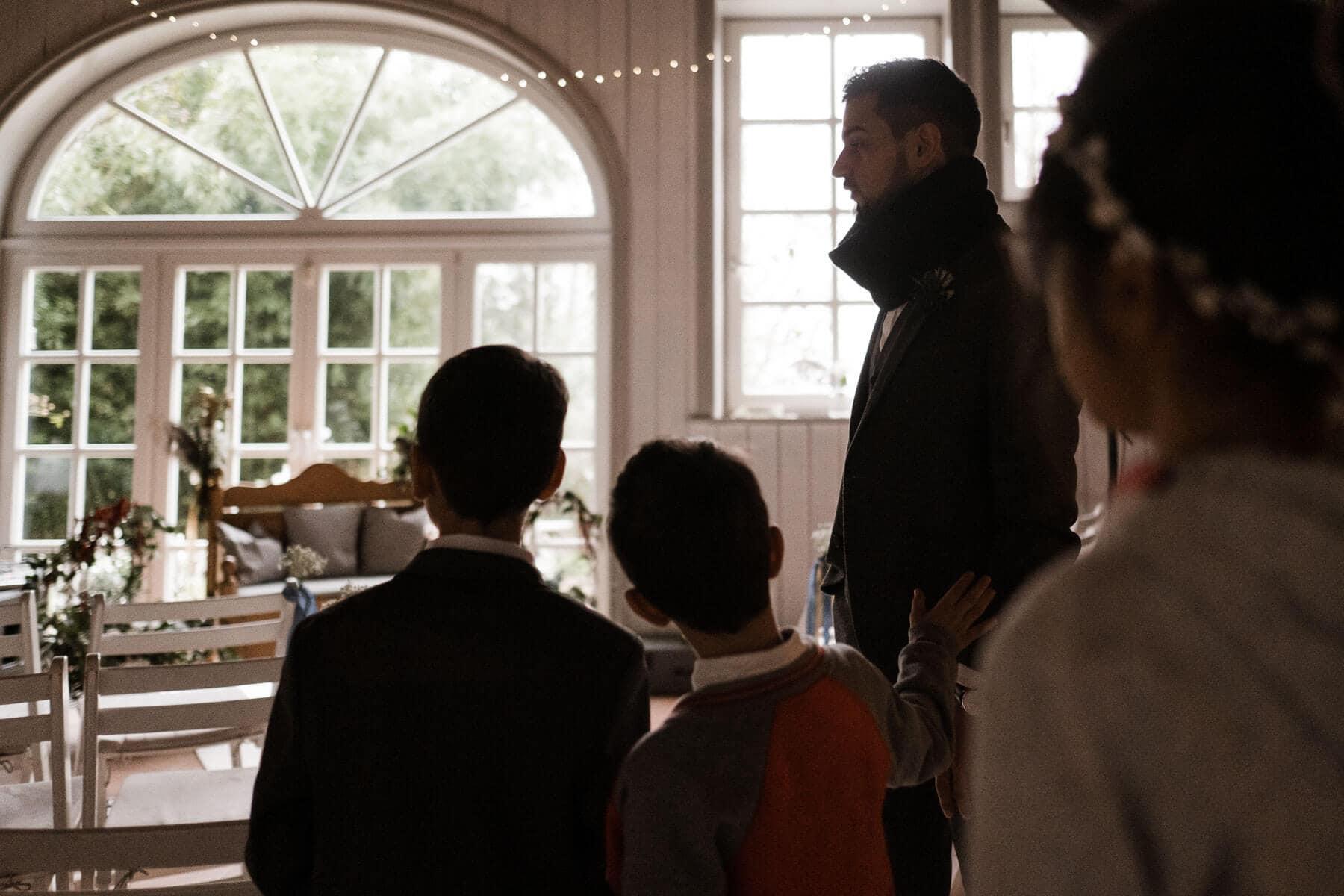 hinter einen großen Türbogen ist die Trauungslocation zu sehen, sie befindet sich in einem Landhaus mit großen, hellen Fenstern mit Sprossen, 2 Jungen und ein Mädchen stehen vor der Tür und blicken in das Zimmer