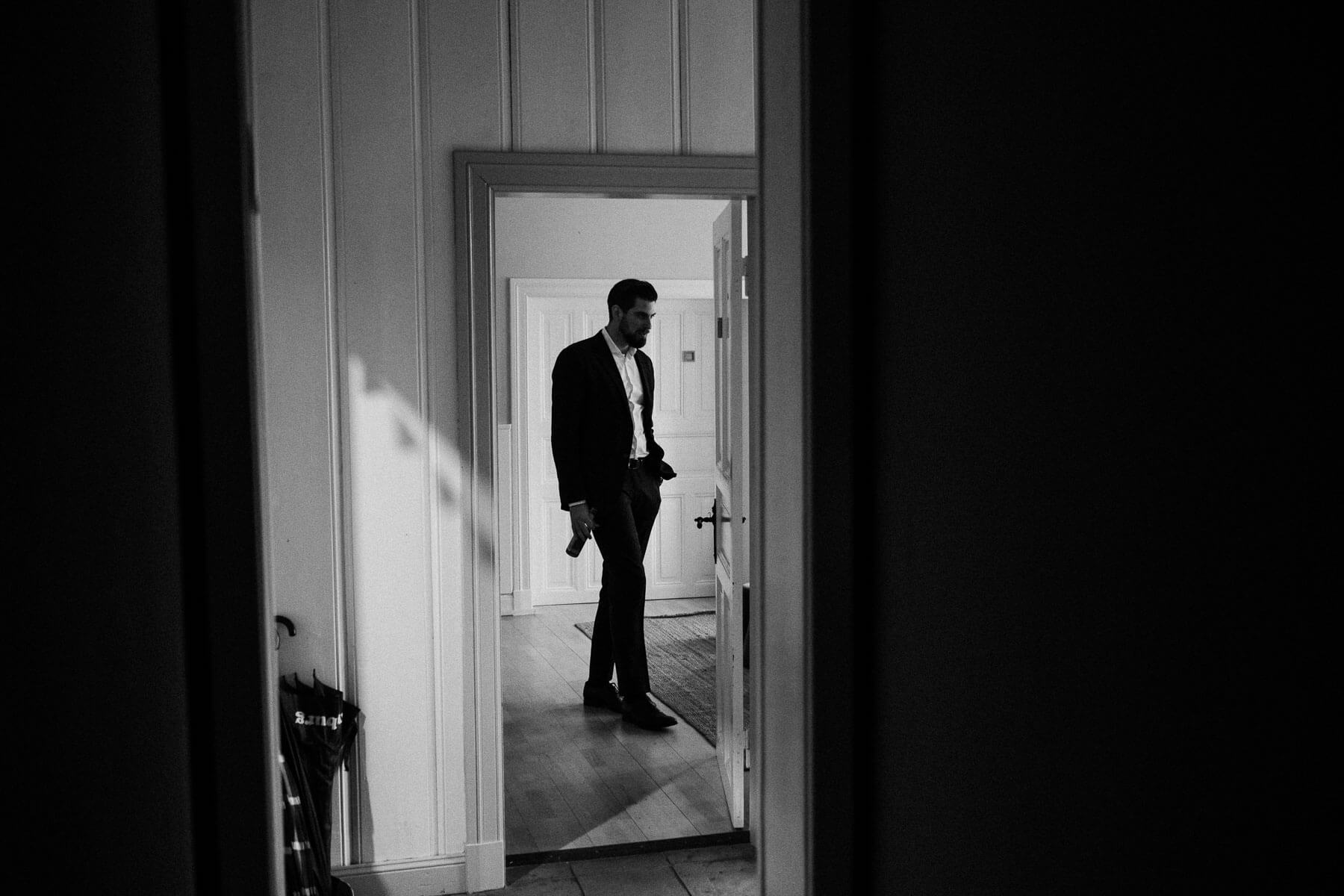 hinter einer offen stehenden Tür in einem Landhaus steht ein Mann in einem schwarzen Anzug, die Tür ist mit Holz verkleidet, die Sonne scheint in das Zimmer