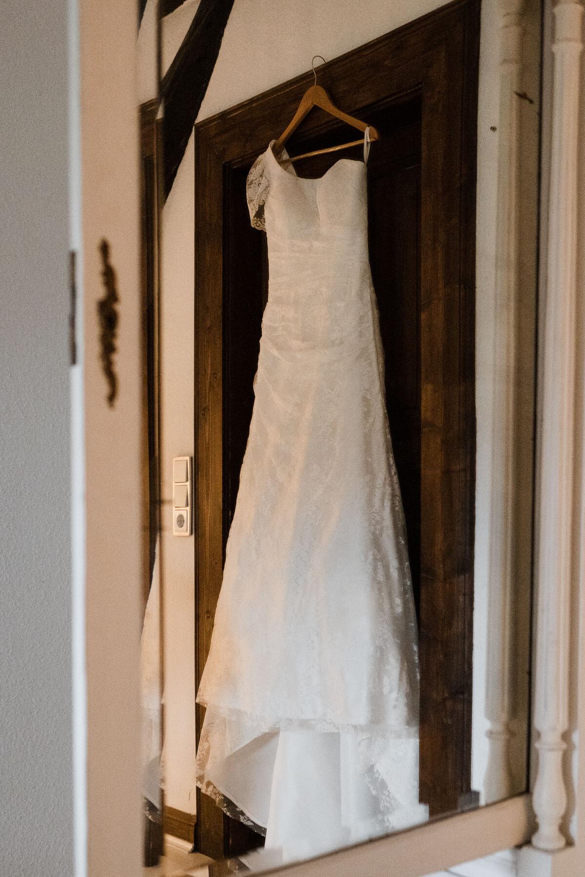 an einer großen, alten Holztür hängt ein weißes Brautkleid an einem Holzbügel