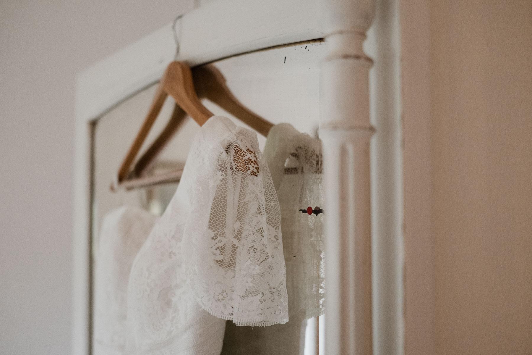 an einer Holztür hangt ein Brautkleid an einem Holzbügel, der kleine Ärmel ist aus einer feinen Spitze
