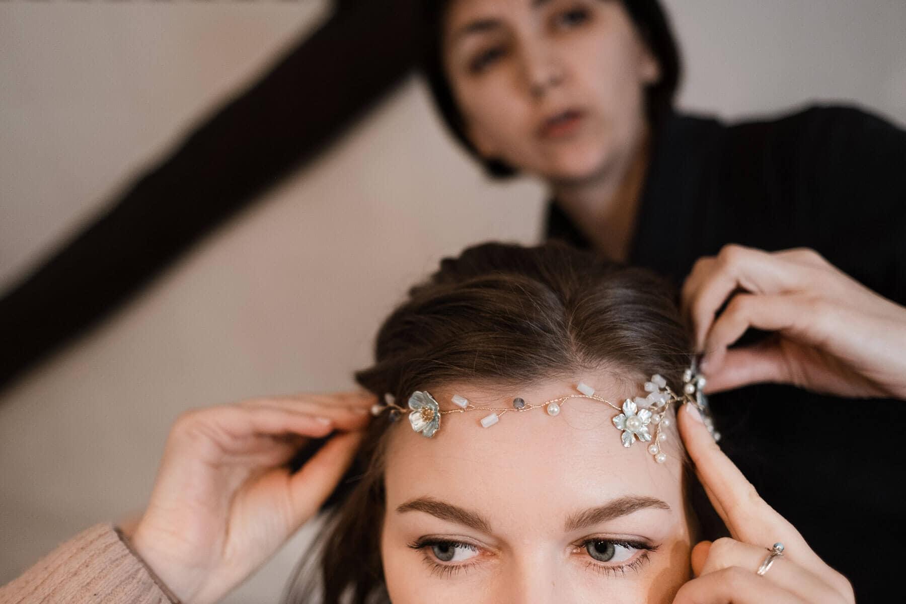 die Braut trägt ein Stirnreif mit kleinen Blumen und Steinen, sie hält den Reif mit beiden Händen fest, hinter ihr steht eine Frau, die ihr den Reif richtet