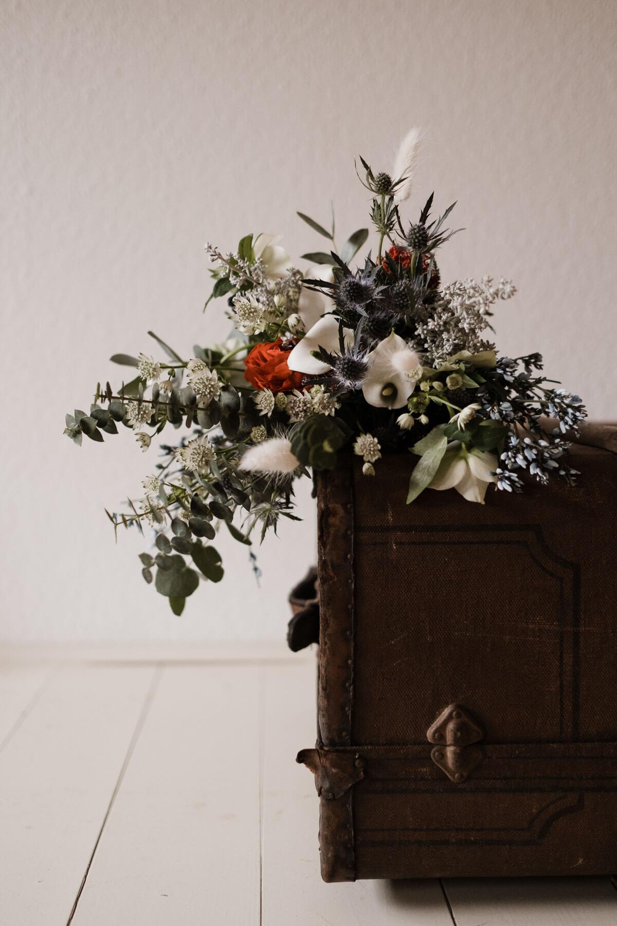 auf einer alten Holzkiste liegt ein großer Blumenstrauß, es sind u.a. Eukalyptus, Ranunkeln, Kugeldiesteln und Pampasgras