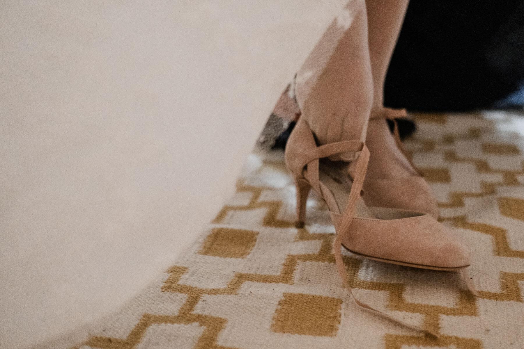 die Braut zieht sich ihre Brautschuhe an, sie haben einen schmalen Absatz, sie werden mit Riemchen befestigt, auf dem Boden liet ein retro- Teppich
