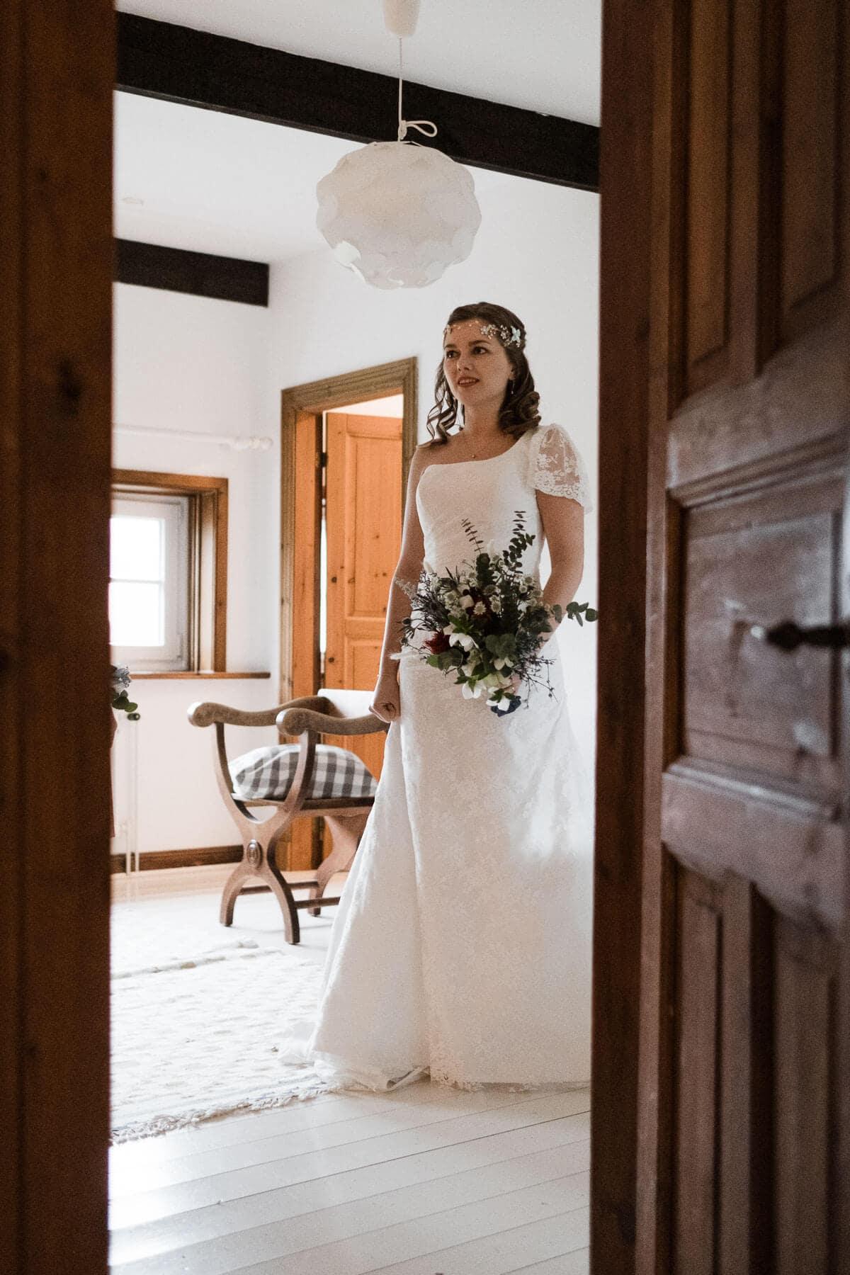 die Braut steht in ihrem Brautkleid in einem Zimmer in einem Landhaus, in ihrer Hand hält sie einen üppigen Blumenstrauß