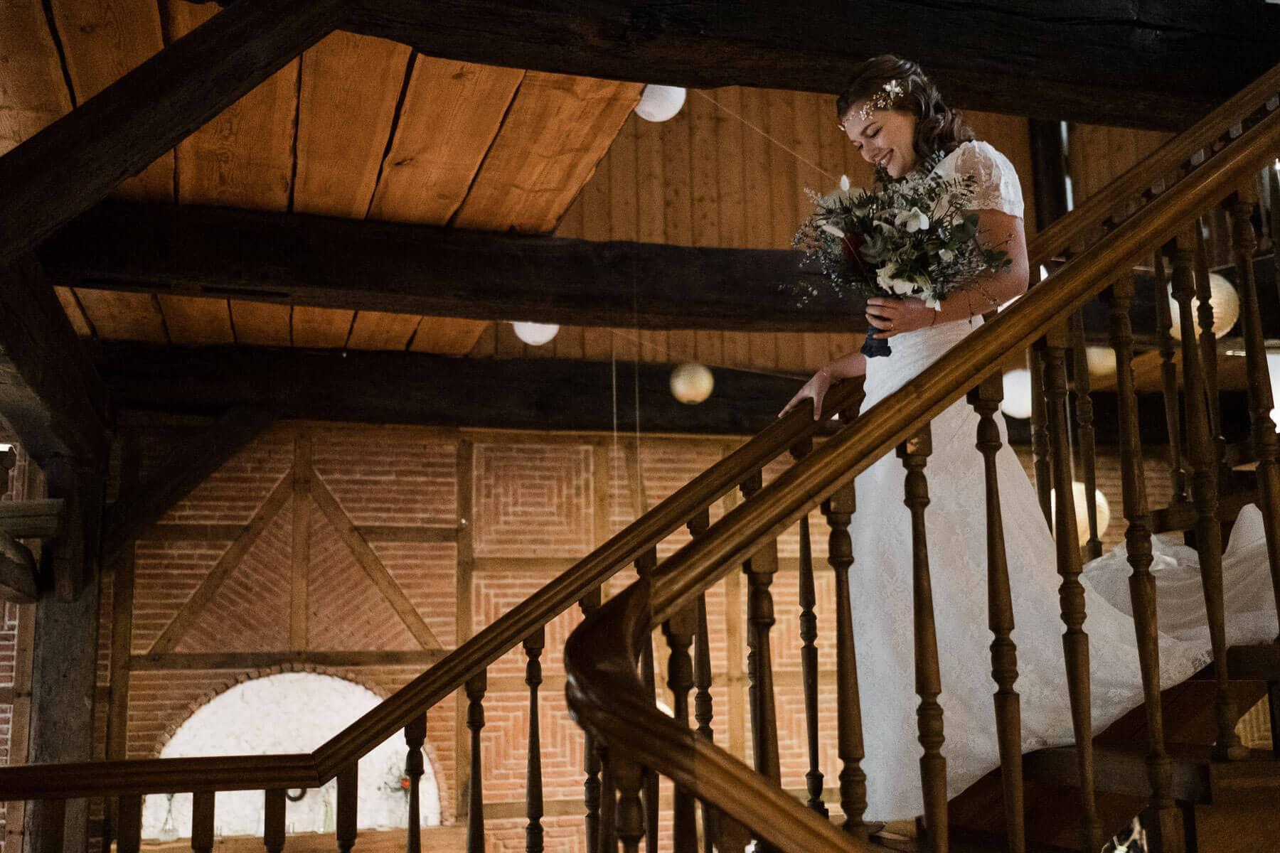 die Braut geht eine alte Holztreppe in einem Landhaus hinunter, an der Decke sieht man Holzgebälk, an er Außenwand ist ein Fachwerk zu sehen, die Braut trägt ein weißes Brautkleid und einen üppigen Blumenstrauß in der Hand, sie schut hinunter auf die Treppen