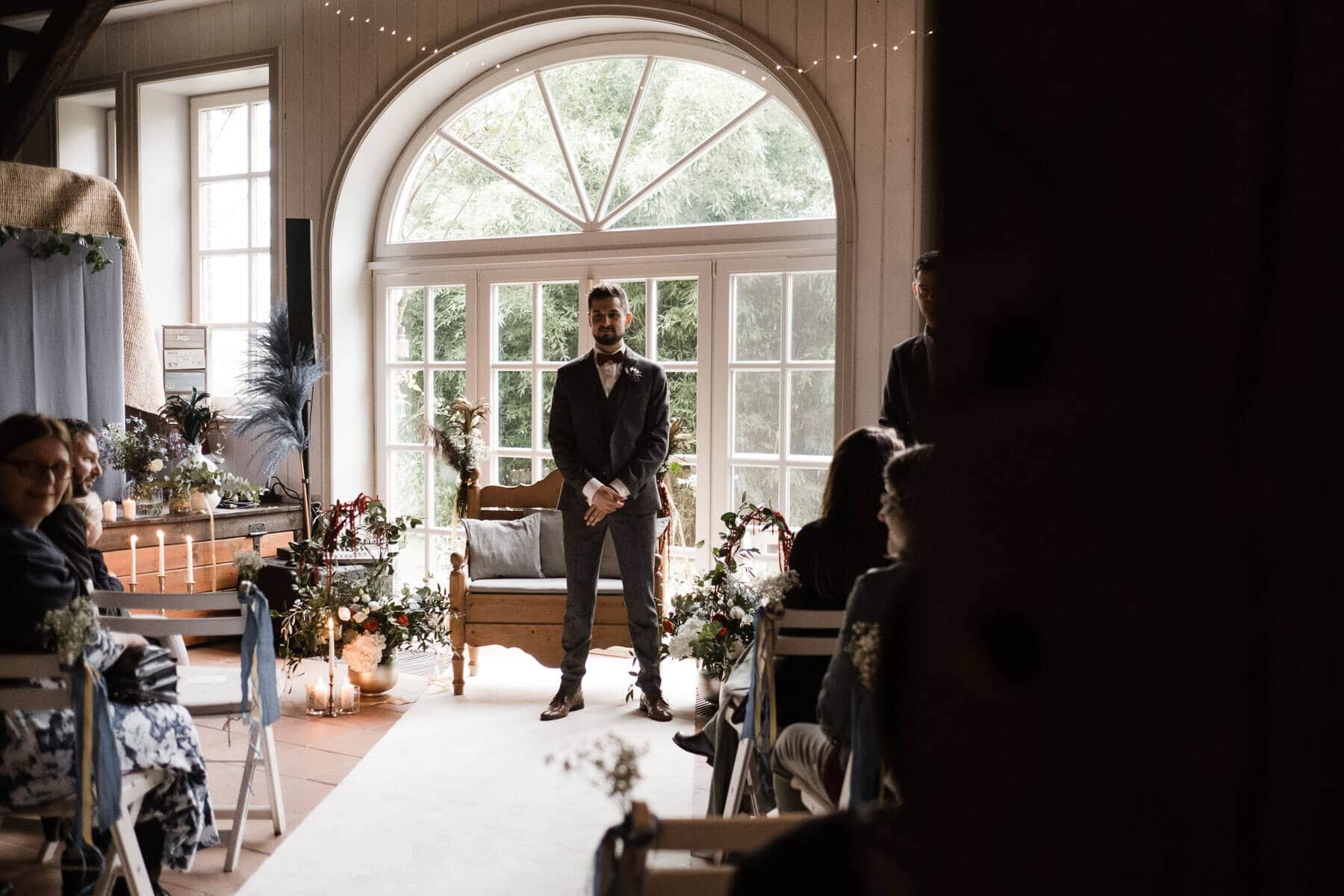 in dem Trauzimmer steht der Bräutigam in einem schwarzen Anzug, er steht vor einer großen, hellen, Flügeltür, die nach drußen ührt, das Zimmer ist mit Blumen und Grünschnitt geschmückt, der Bräutigam hält seine Arme vor seinen Körper, sein Blick ist in Richtung der Kamera gerichtet,