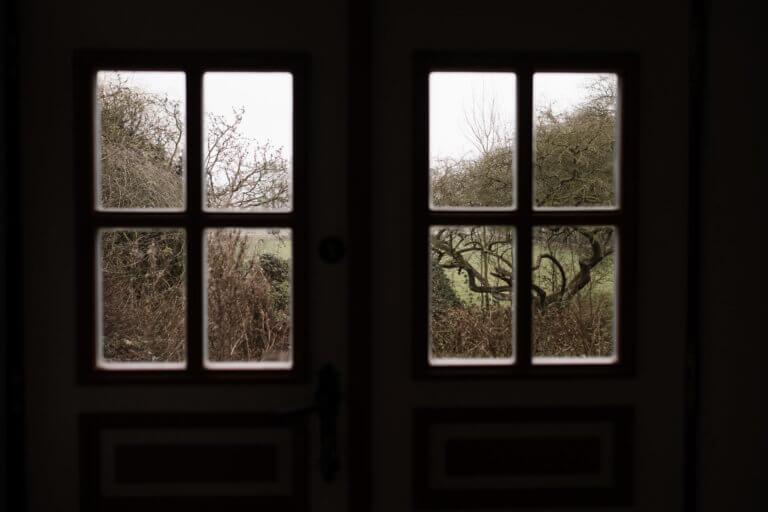 der Blick aus einem großen, breiten Holzfenster mit Sprossen, der Blick ist auf kahle Bäume und einen kahlen Garten