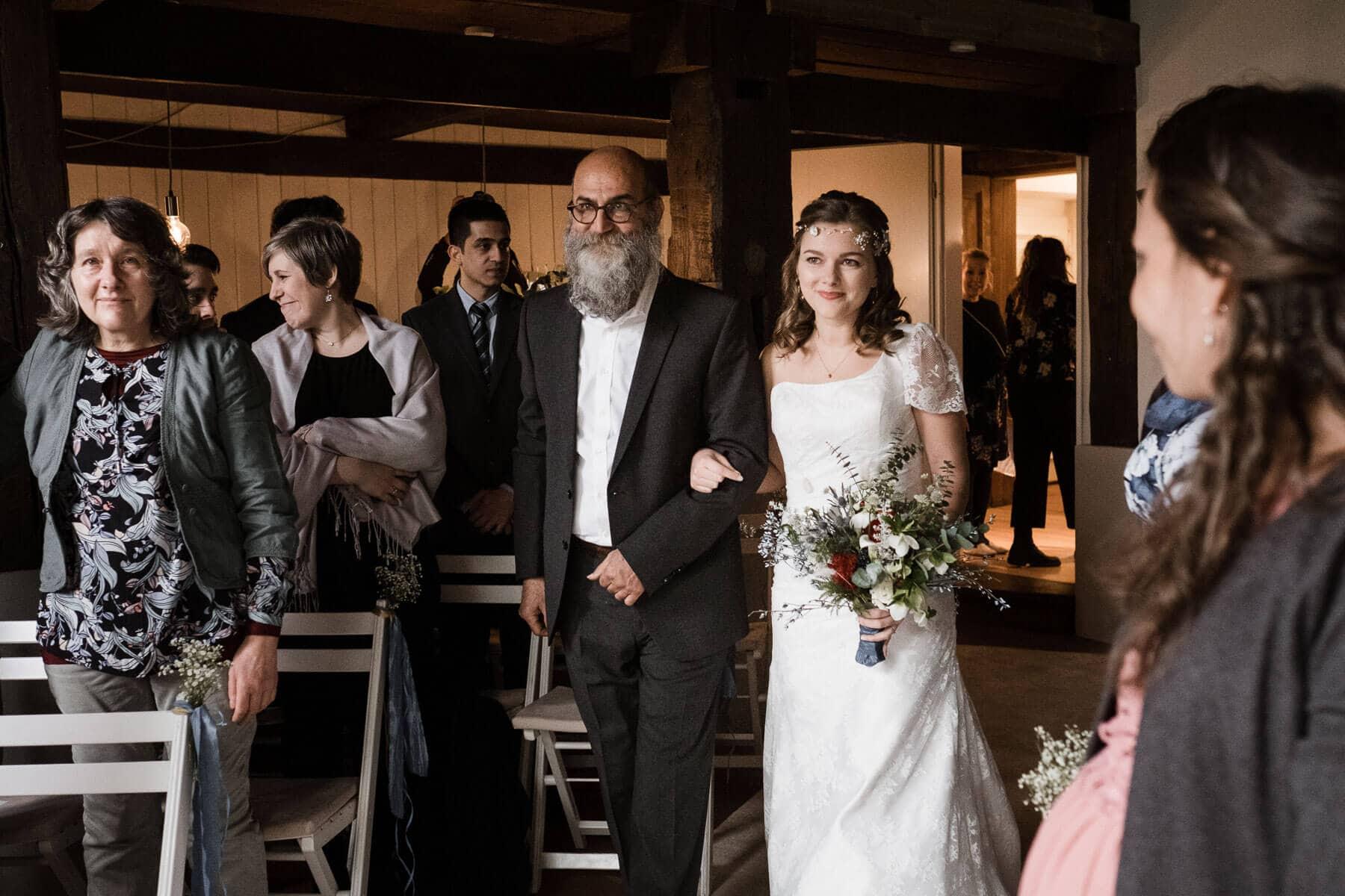 die Braut kommt mit ihrem Brautvater in das Trauzimmer in dem Landhaus, sie trägt ein weißes Brautkleid und hat einen üppigen Brautstrauß in der Hand, der Brautvater trägt einen schwarzen Anzug und hat einen langen Bart, sie gehen durch einen Gang, um sie herum stehen die Gäste