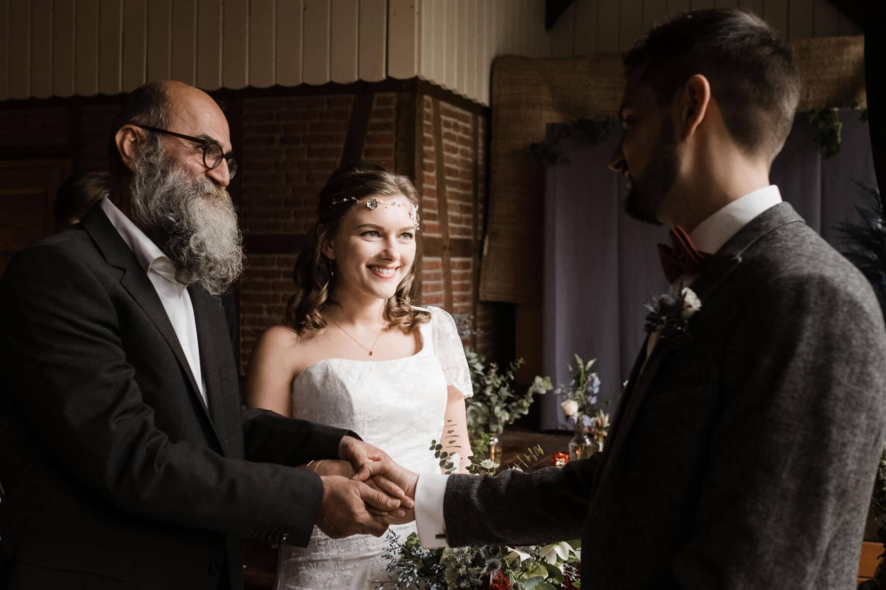 der Brautvater bringt die Braut zu dem Bräutigam, er legt die Hand des Bräutigam auf die Hand der Braut, sie stehen in einem Zimmer mit Fachwerk in einem Landhaus