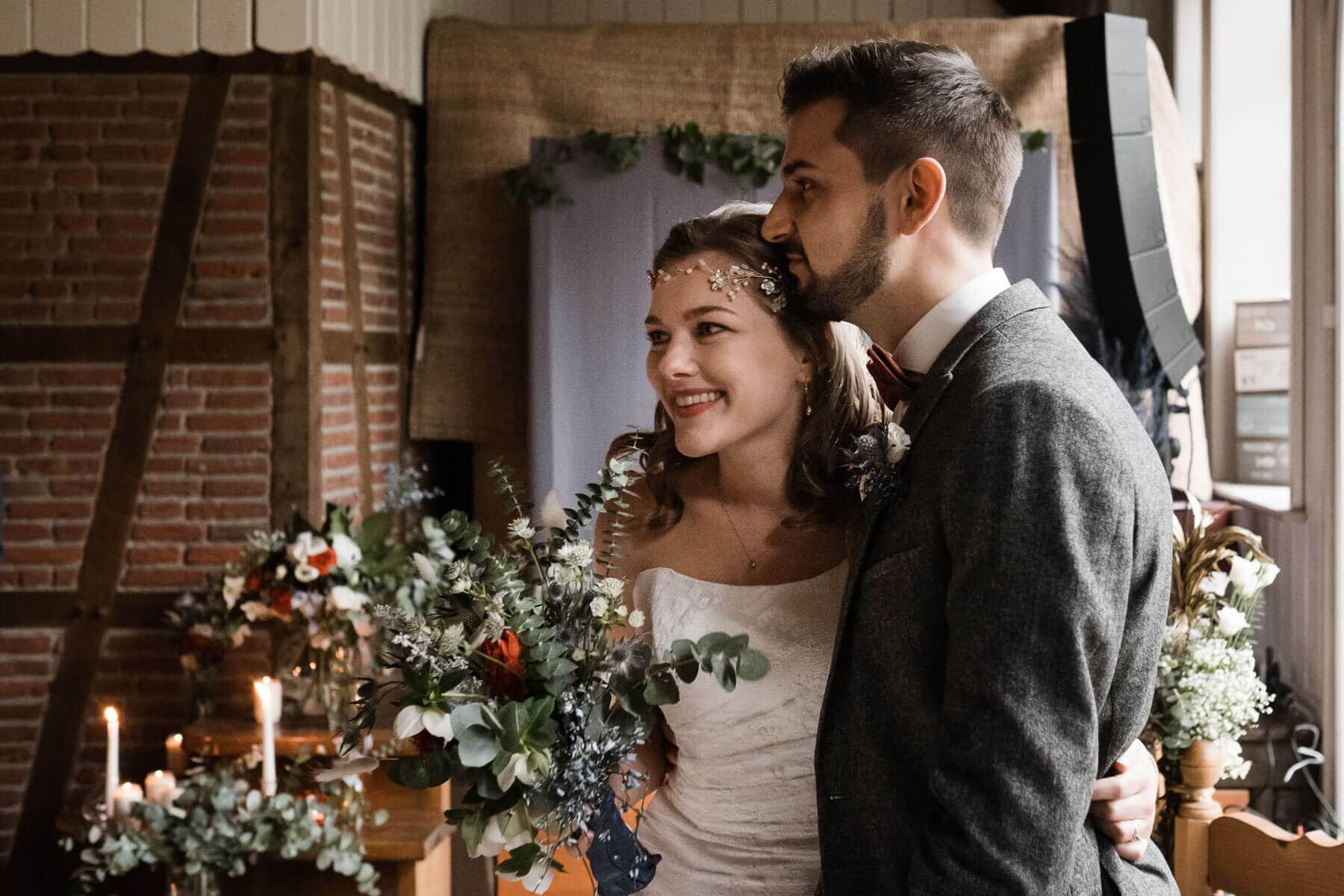 die Braut und der Bräutgam stehen in dem Trauzimmer mit Fachwerk in einem Landhaus, der Mann hält sie seitlich im Arm, sie schauen in Richtung der Gäste