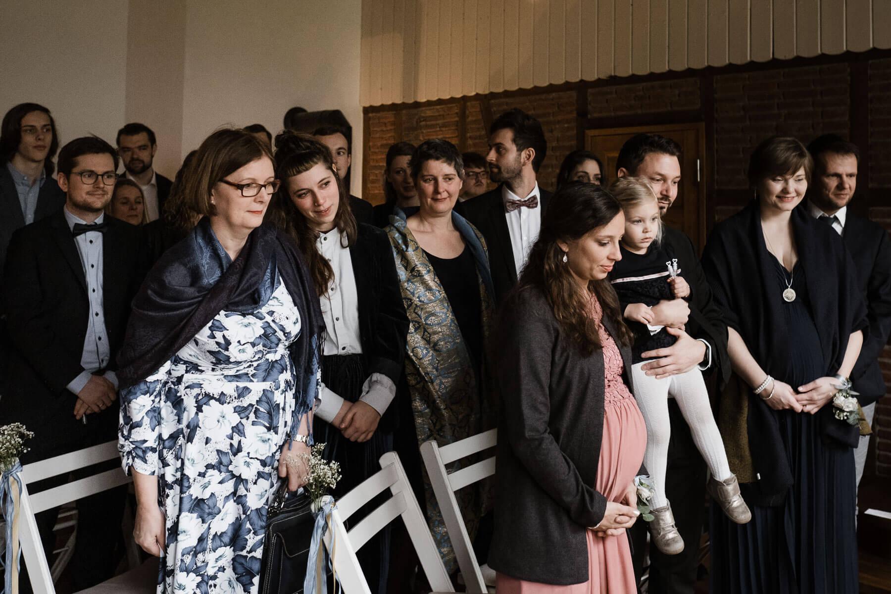 einige Gäste stehen in dem Trauzimmer in dem Landhaus, hinter ihnen stehen weiße Klappstühle