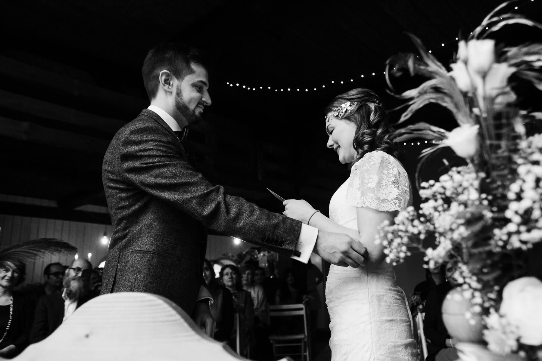 ein Brautpaar steht sich gegenüber, der Bräutigam hält seine Arme an die Arm der Braut, die Brut hält einen Zettel in der Hand, der Bräutigam schaut auf die Brut, um sie herum stehen Blumengestecke