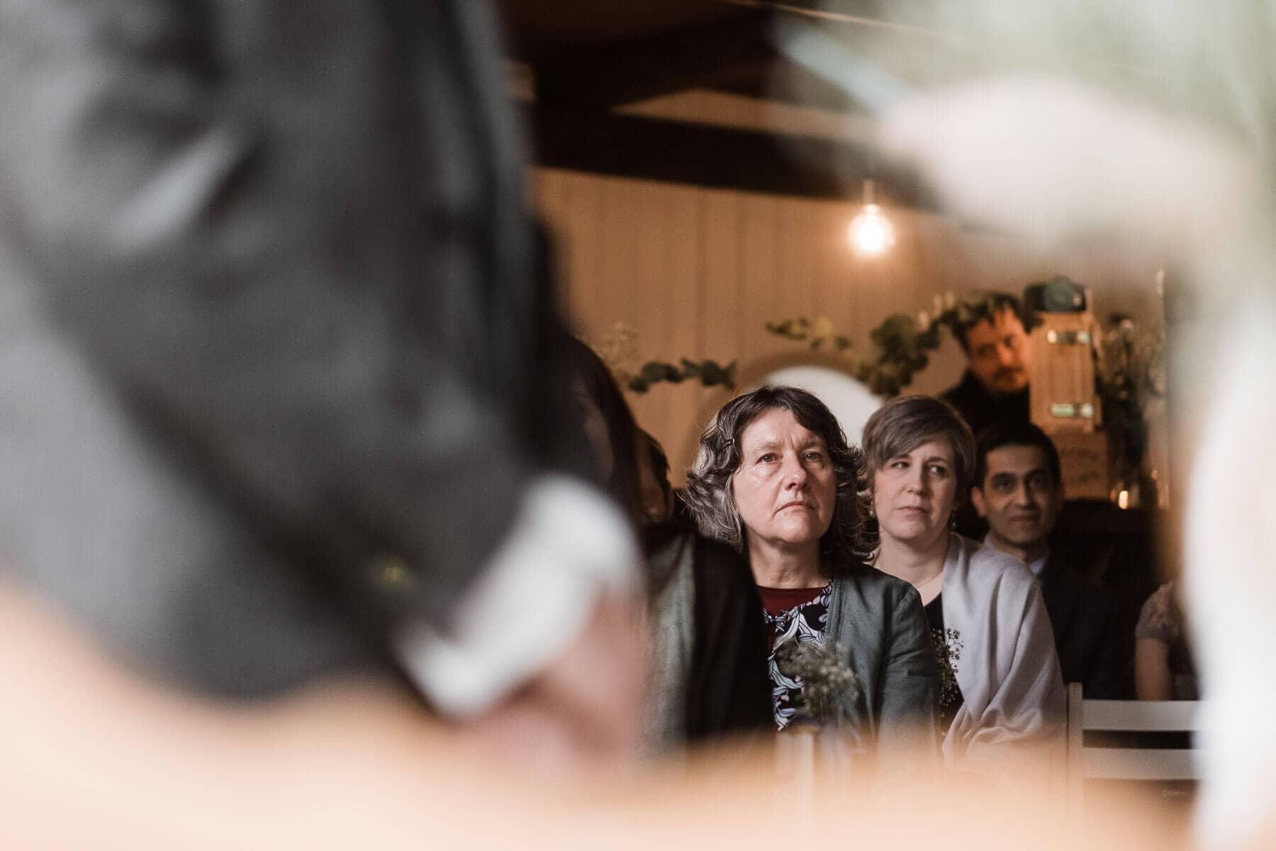 im Hintergrund des Brautpaar sitzen die Gäste des Brautpaar, sie schauen aufmerksam auf das Brautpaar