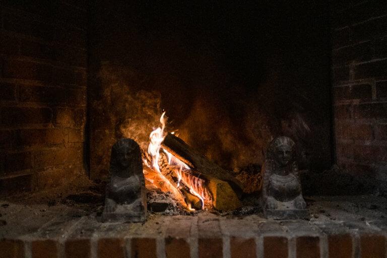 ein Feuer brennt in einem Steinkamin in einem Landhaus
