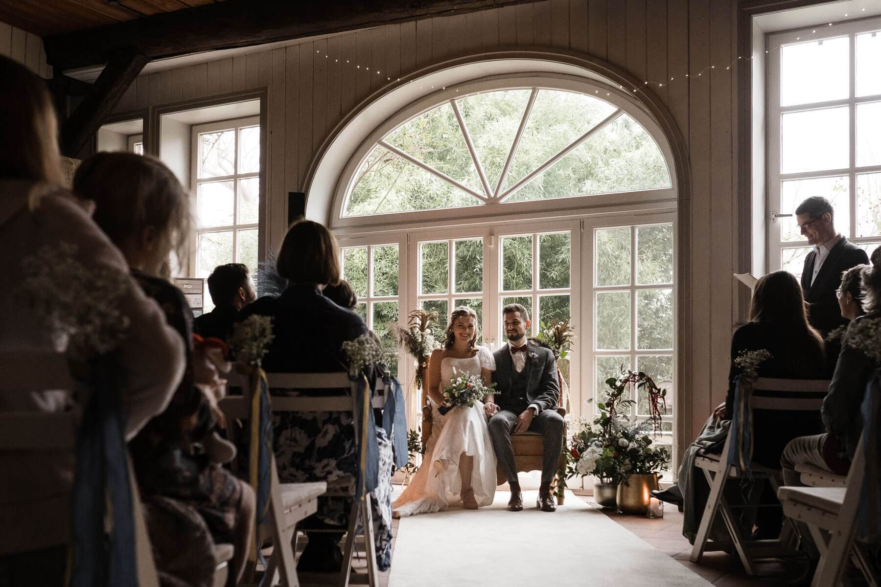 vor einer großen, hellen Bogentür in einem Landhaus steht eine geschmückt Holzbank, auf der ein Brautpaar sitzt, das Brautpaar sitzt in Richung der Gäste, die auf weißen Holzklappstühlen sitzen