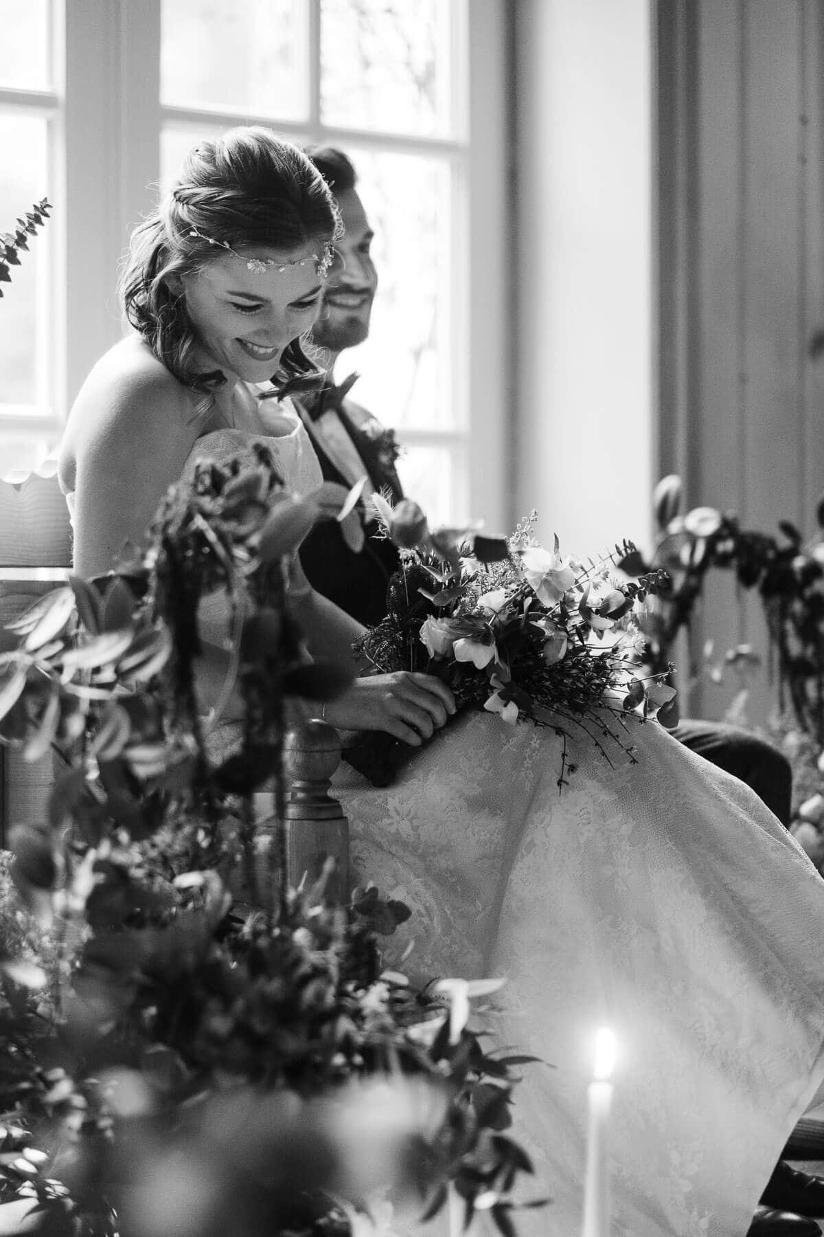 das Brutpaar sitzt auf einer Holzbank in einem Zimmer mit großen, helen Fenstern in einem Landhaus, di Bank ist geschmückt, die Braut schaut hinunter auf den Boden