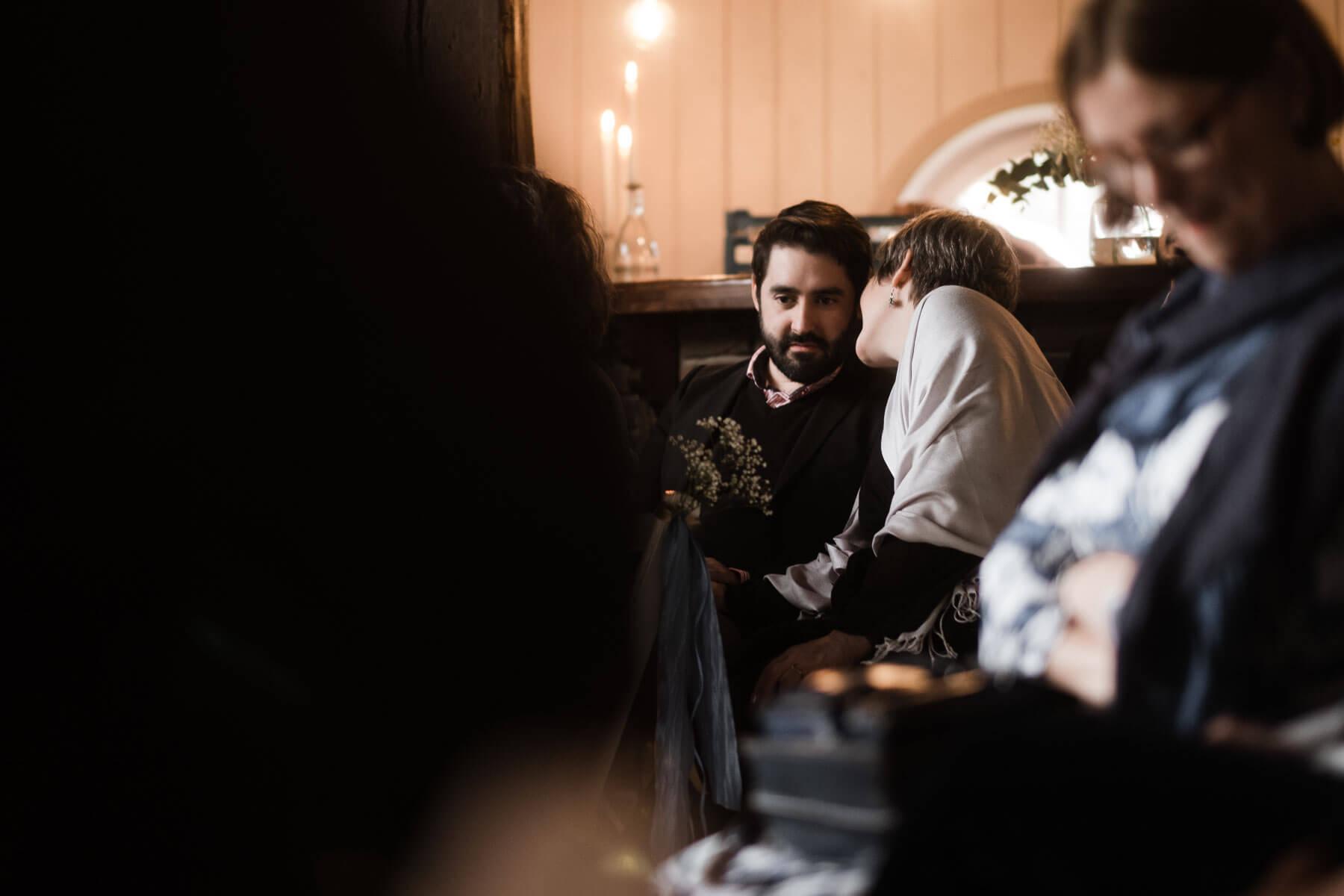 in einem Trauzmmer in einem Landhaus sitzen die Gäste des Brautpaar, eine Frau flüstert einem Mann etwas ins Ohr