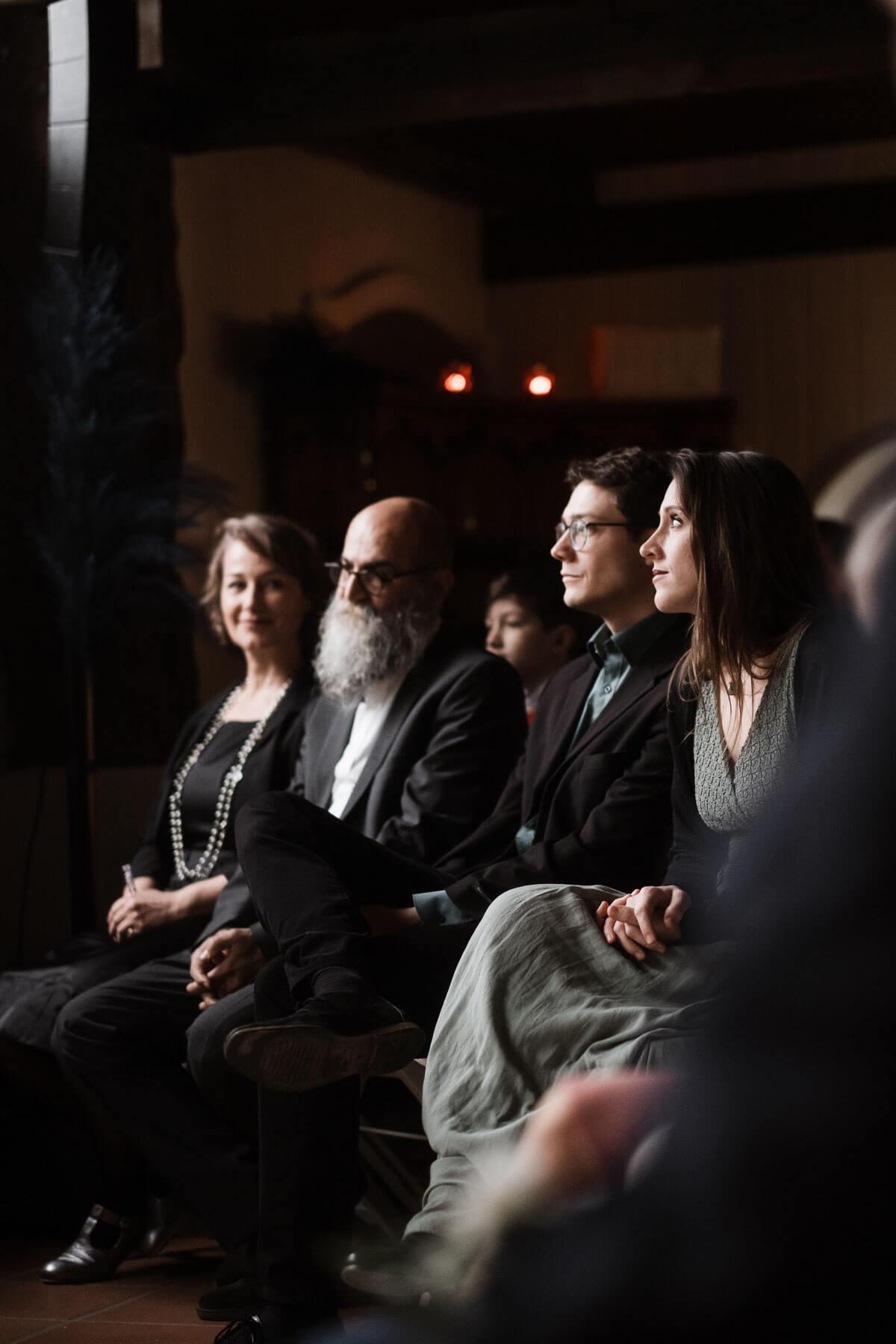 in einem Trauzimer in einem Landhaus sitzen die Gäste des Brautpaar, sie schauen aufmerksam auf das Brautpaar