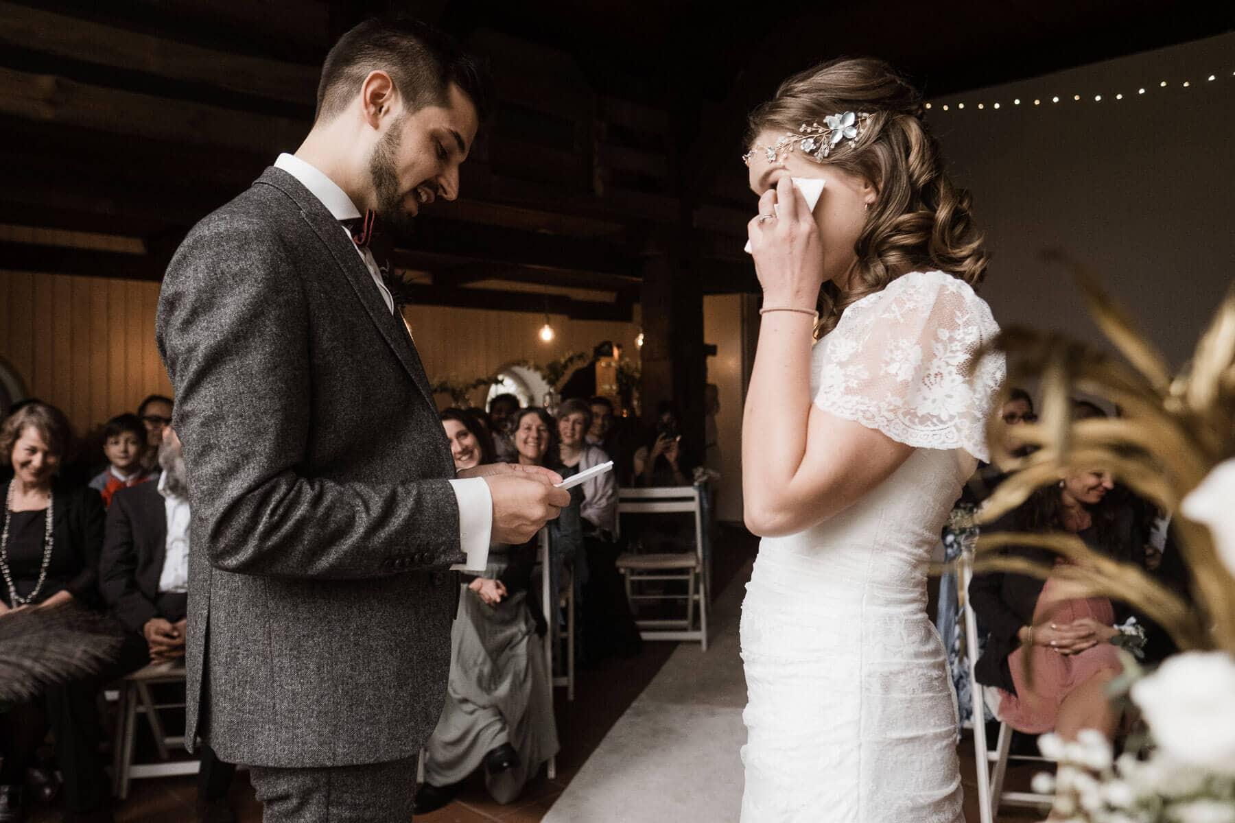 das Brautpaar steht in dem Trauzimmer eines Landhaus, im Hintergrund sitzen die Gäste des Brautpaar, der Bräutigam hält einen Zettel in der Hand, die Braut hält sich ein Taschentuch an die Wange