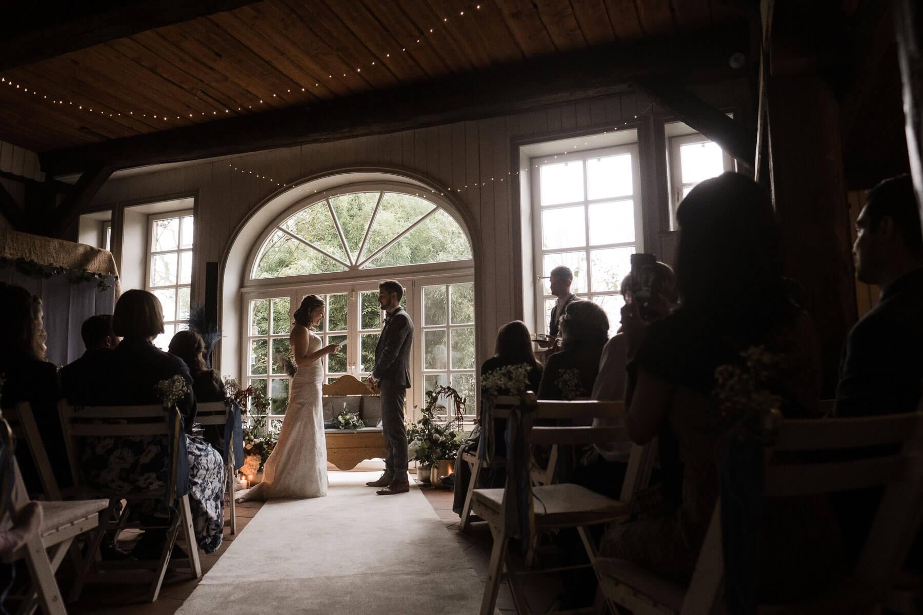 vor einer großen, hellen Flügeltür in einem Landhaus steht ein Brautpaar, hinter ihnen sitzen einige Gäste auf weißen Holzklappstühlen, die Braut hält einen Zettel in ihrer Hand