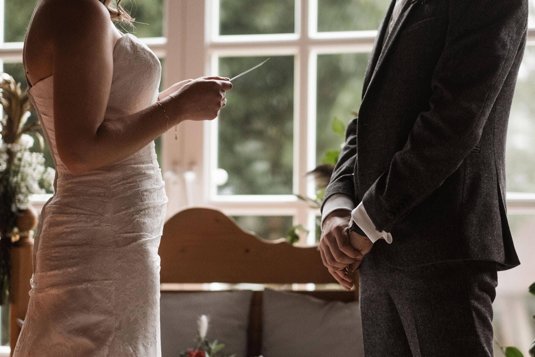 vor einer großen, hellen Holztür steht ein Brautpaar, das Brautpaar steht sich gegenüber, die Braut hält einen Zettl in der Hand, der Bräutigam hält seine Arme verschränkt vor seinen Körper