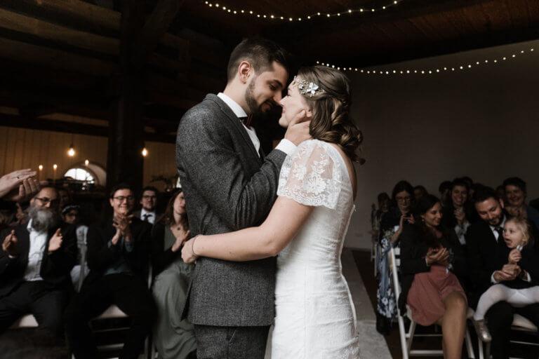 ein Brautpaar steht in einem Trauzimmer in einem Landhaus, sie stehen sich gegenüber, er hält seine Hände an ihr Gesicht, sie hält ihre Arme um seinen Bauch, im Hintergrund sitzen die Gäste und schauen auf das Brautpaar