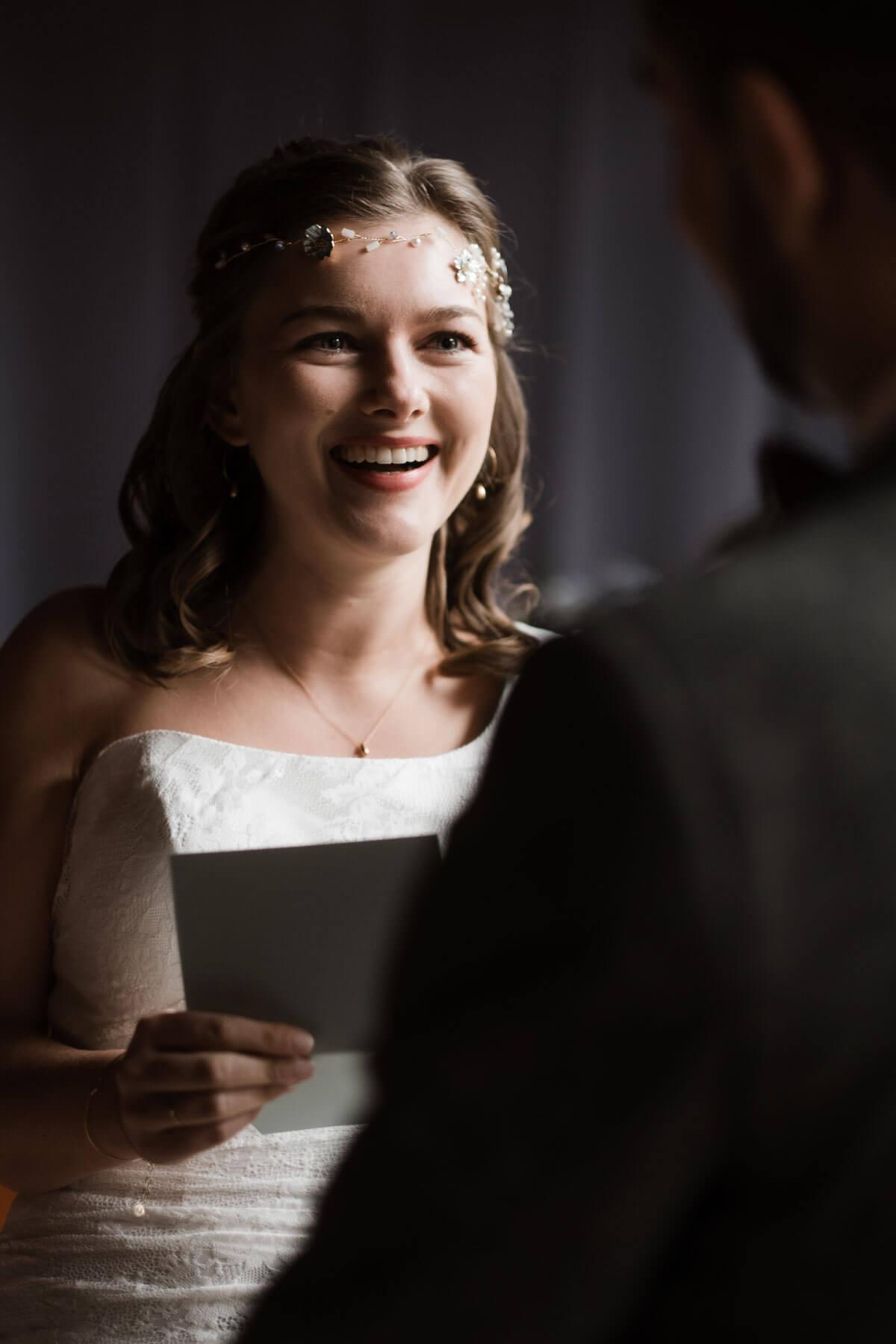 das Brautpar steht sich gegenüber in einem Trauzimmer in einem Landhaus, die Braut hält einen Zettel in der Hand und lacht