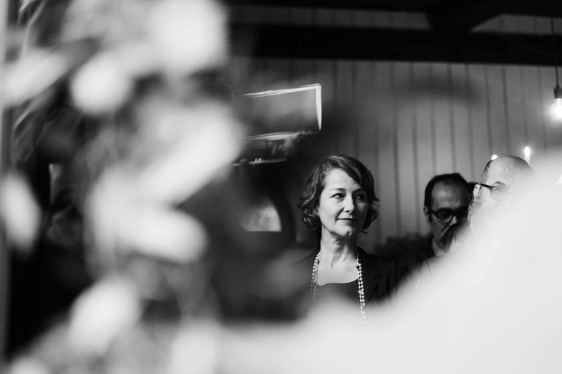 in einem Trauzimmer in einem Landhaus sitzen die Gäste des Brautpaar, eine Frau und ein Mann schauen aufmerksam auf das Brautpaar, im Vordergund steht ein Blumengesteck