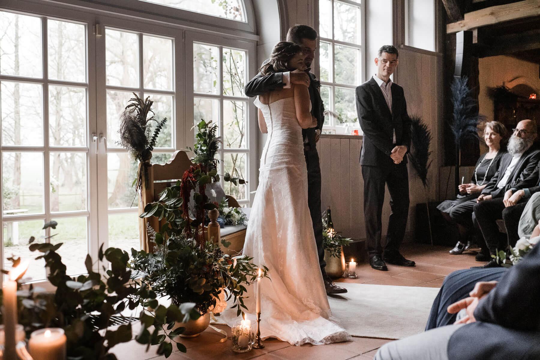 das Brautpaar steht vo einer goßen, hellen Bogentür in einem Landhaus, der Bräutigam legt seine Arm um die Braut, sie schauen in die Richtung ihrer Gäste