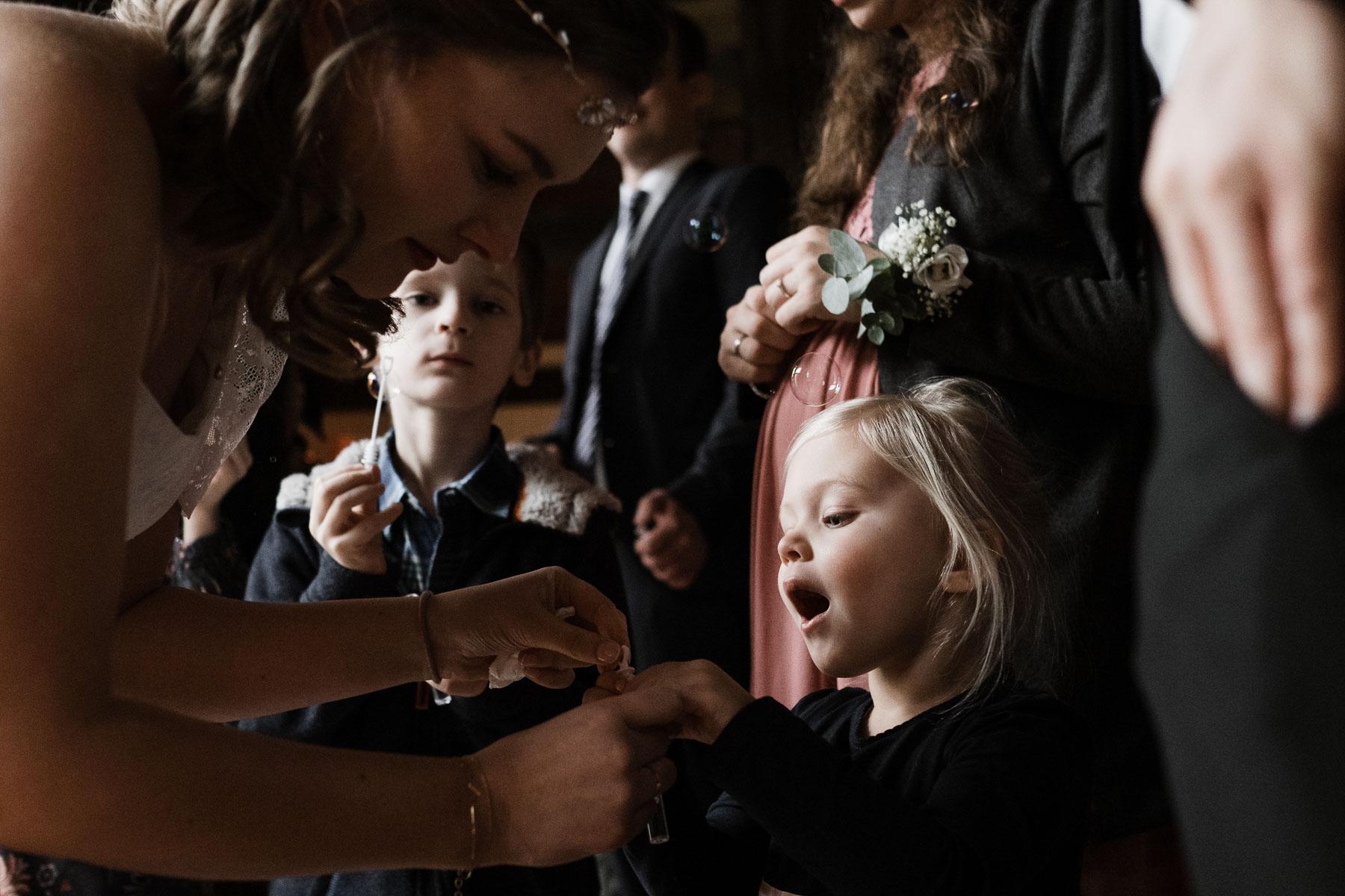 die Braut bückt sich nach unten zu einem kleinen Mädchen, das Mädchen öffnet den Mund, um sie herum stehen andere Gäste